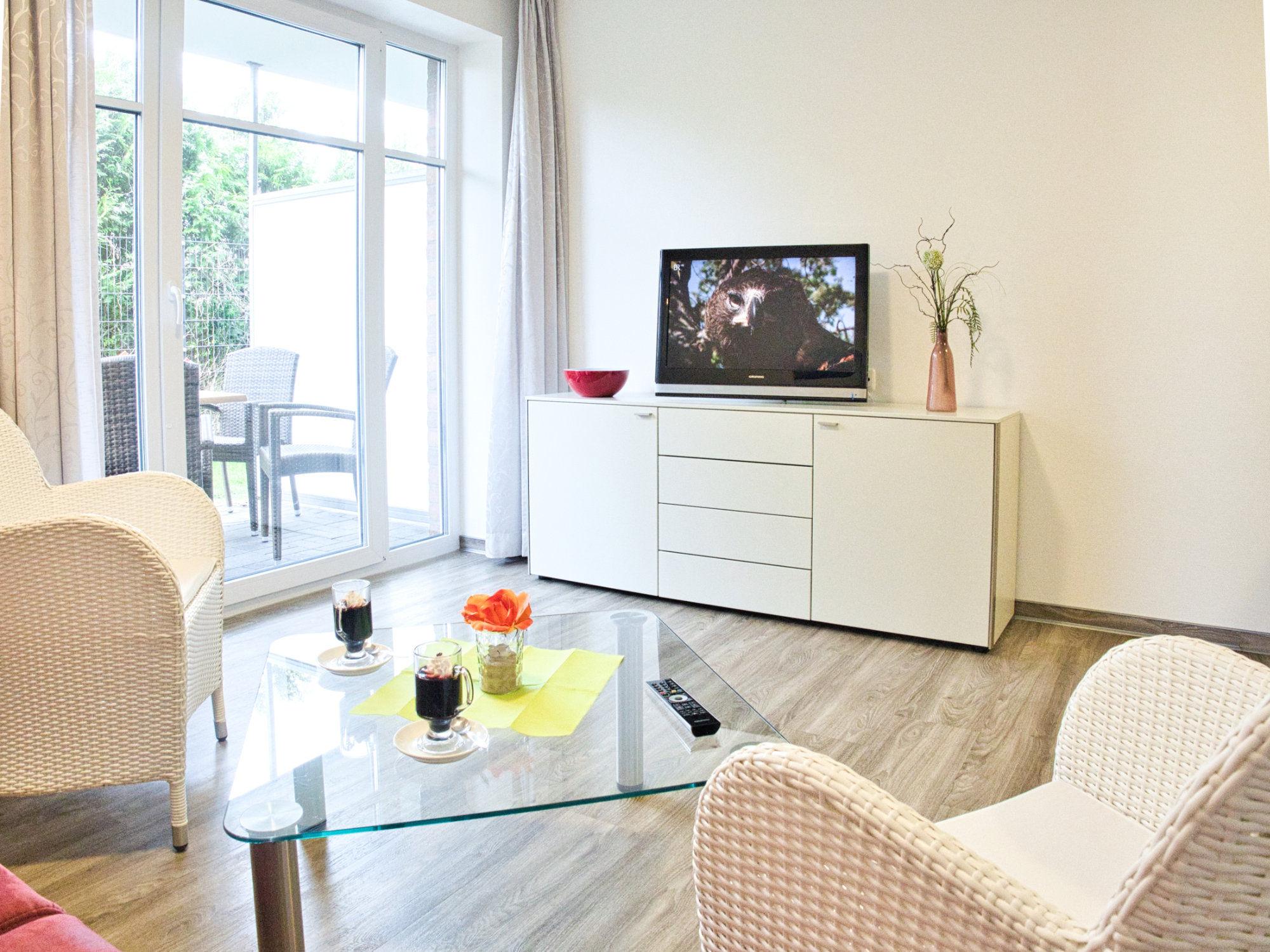 Wohnzimmer mit Couch, Glastisch, 2 Korbsesseln, Sideboard und Flatscreen TV, große Terrassentür