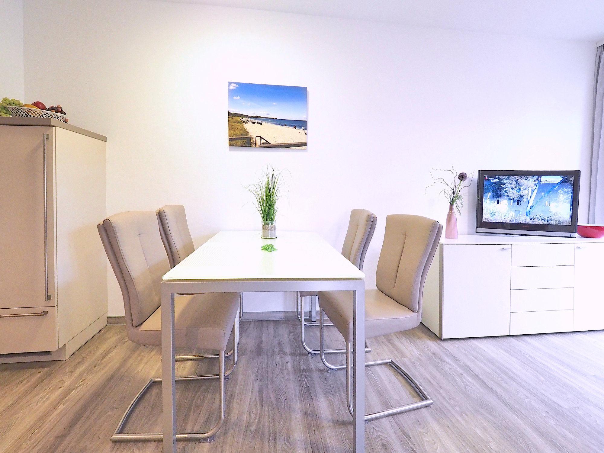 Esstisch mit vier Stühlen, rechts davon Sideboard mit Flatscreen TV