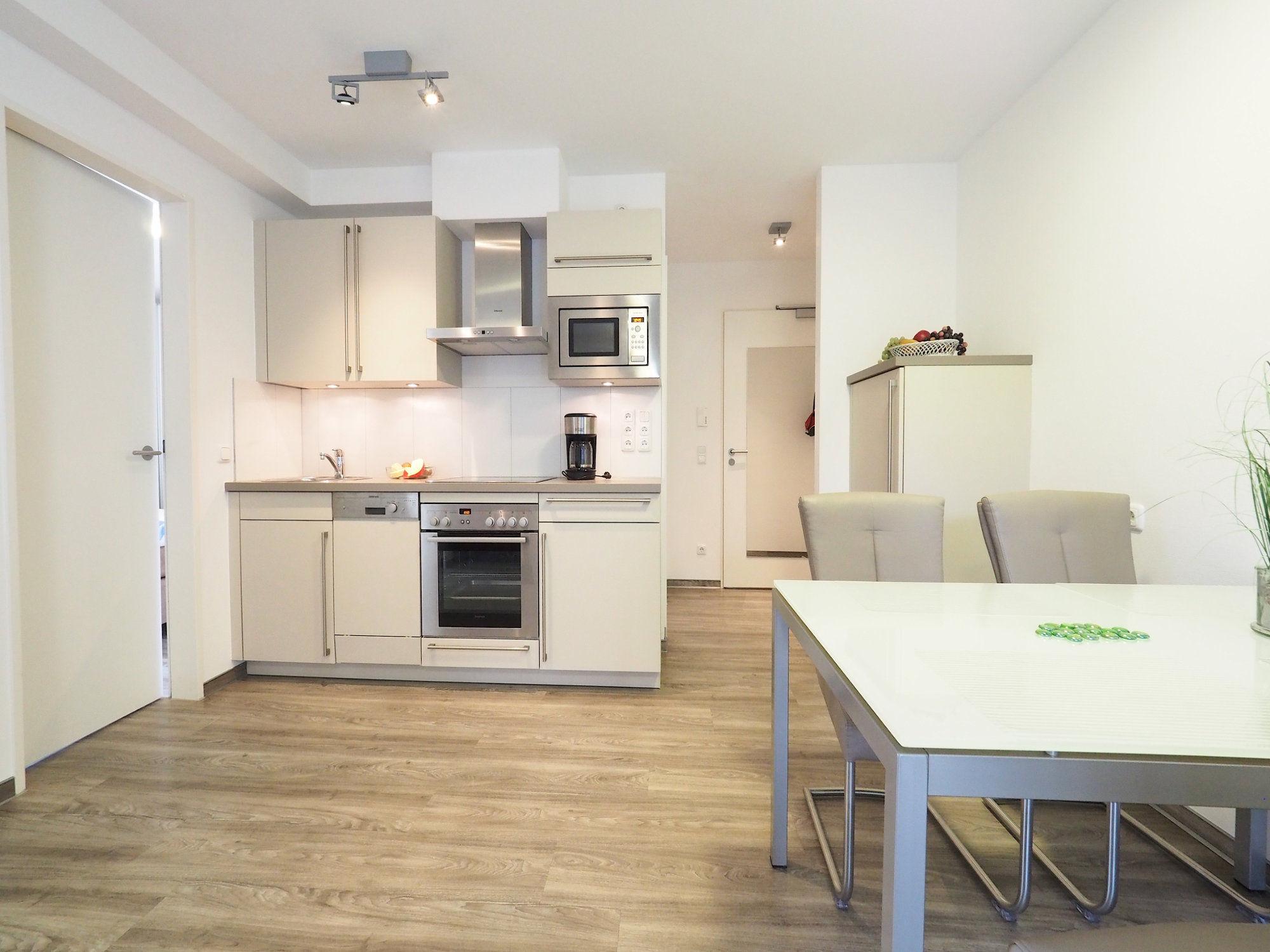 Esstisch mit Stühlen auf der rechten Seite, links im Hintergrund moderne Küchenzeile
