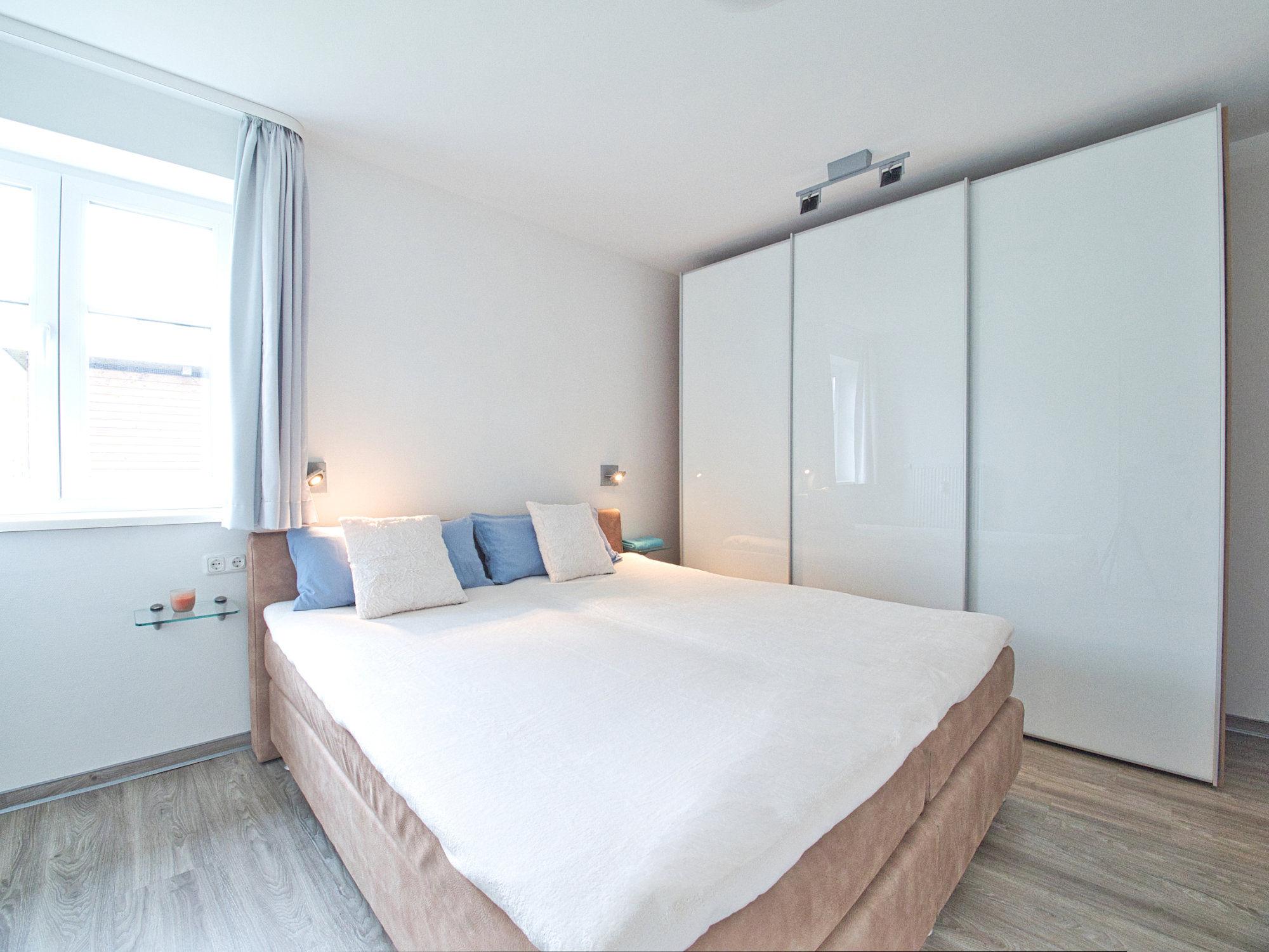 Schlafzimmer mit Doppelbett,   Kleiderschrank und Fenster