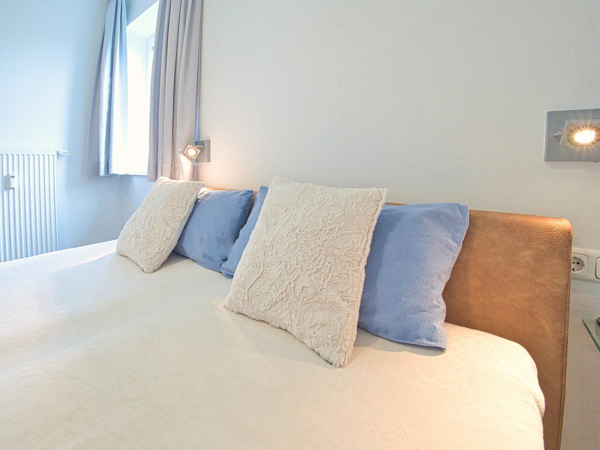 Schlafzimmer mit Doppelbett,  Blick auf das Kopfteil mit Kissen und Fenster
