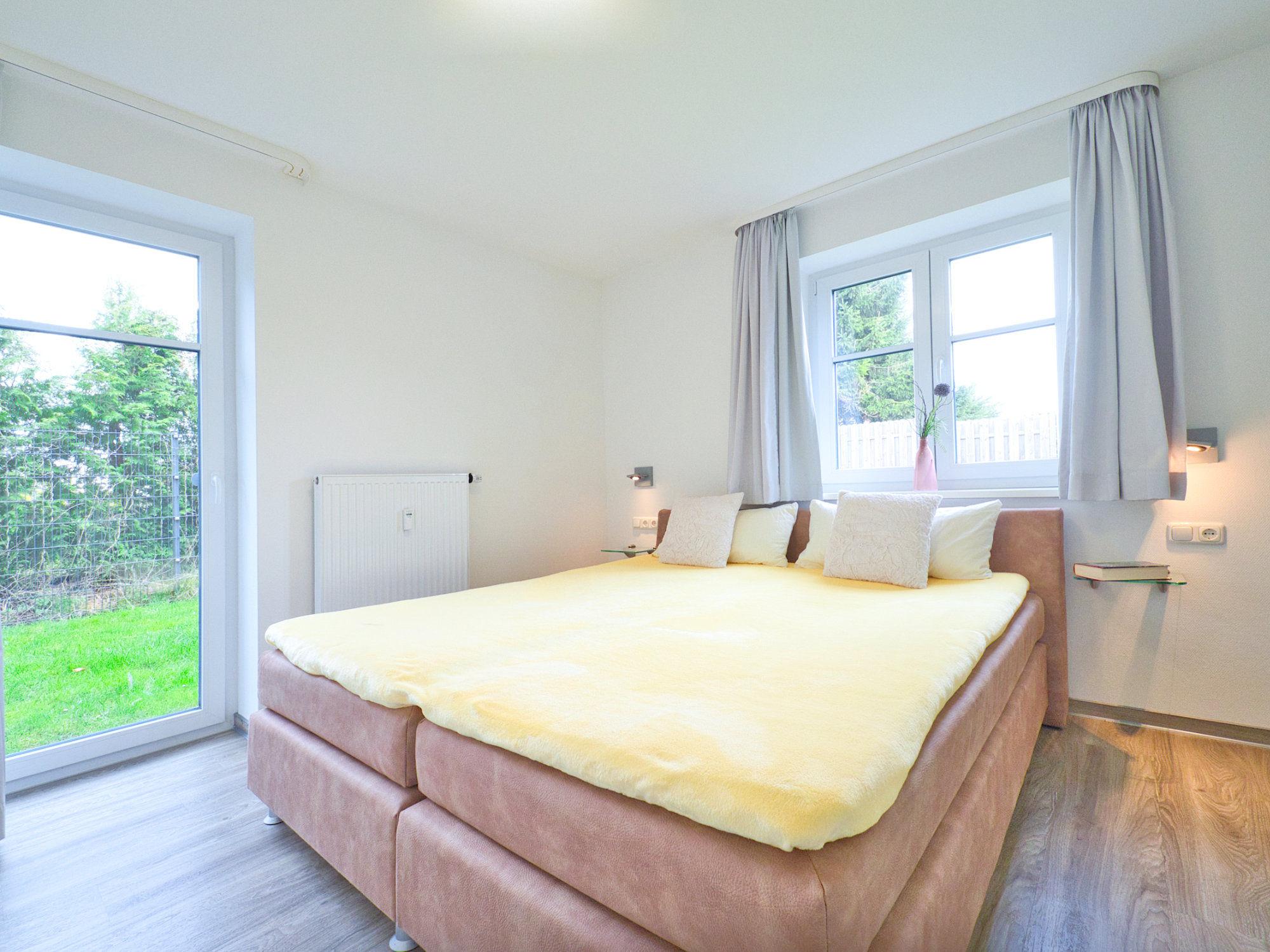 Zweites Schlafzimmer mit Doppelbett, Fenster und großer Terrassentür