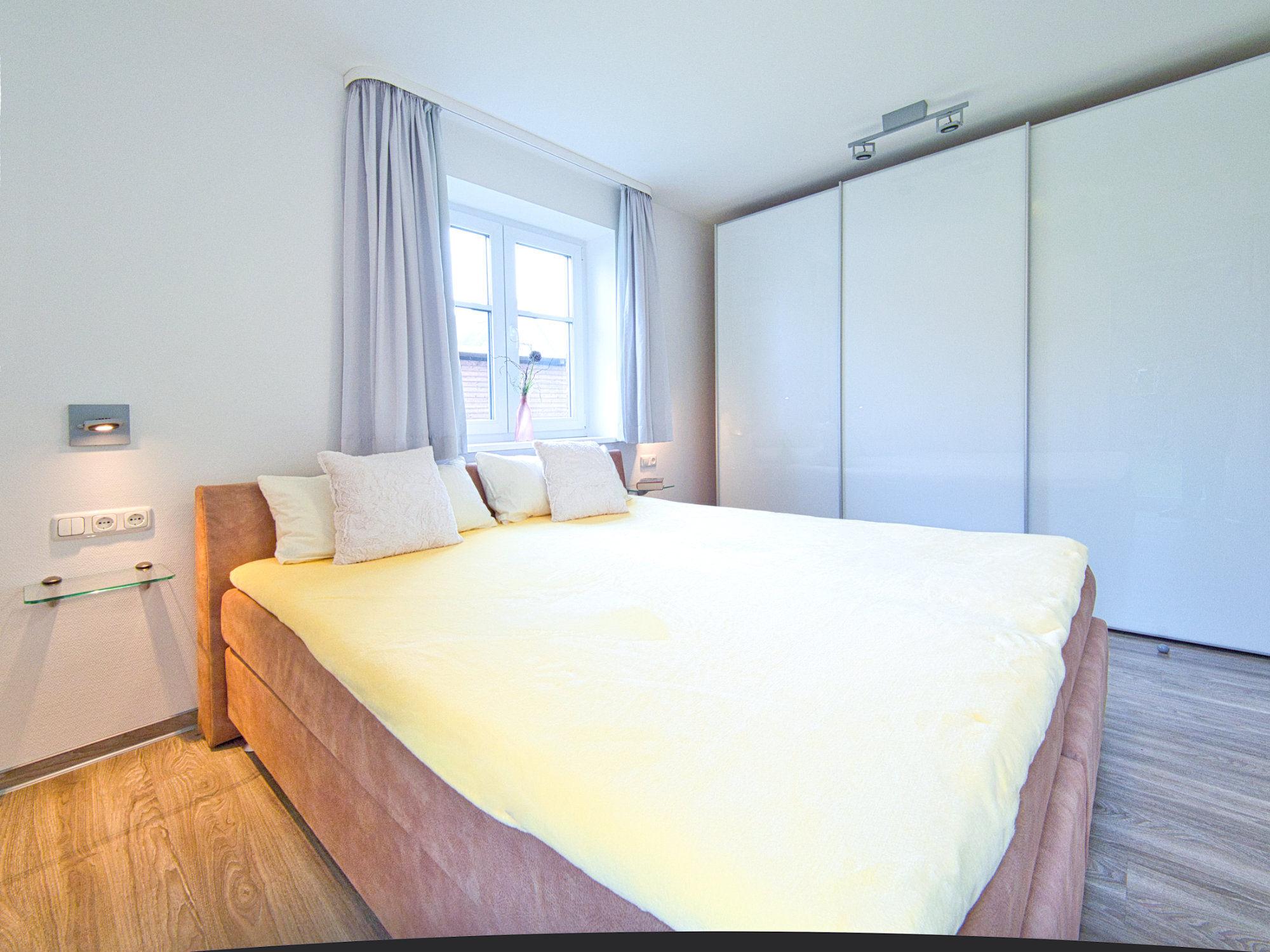 Zweites Schlafzimmer mit Doppelbett. Rechts davon ein Fenster und ein Kleiderschrank