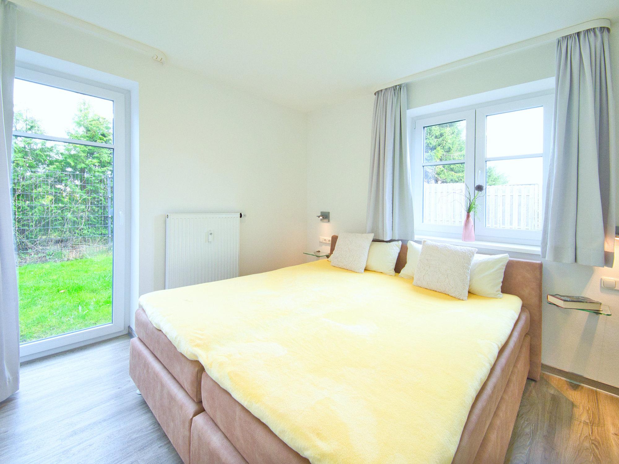 Zweites Schlafzimmer mit Doppelbett, einem Fenster und einer Terrassentür