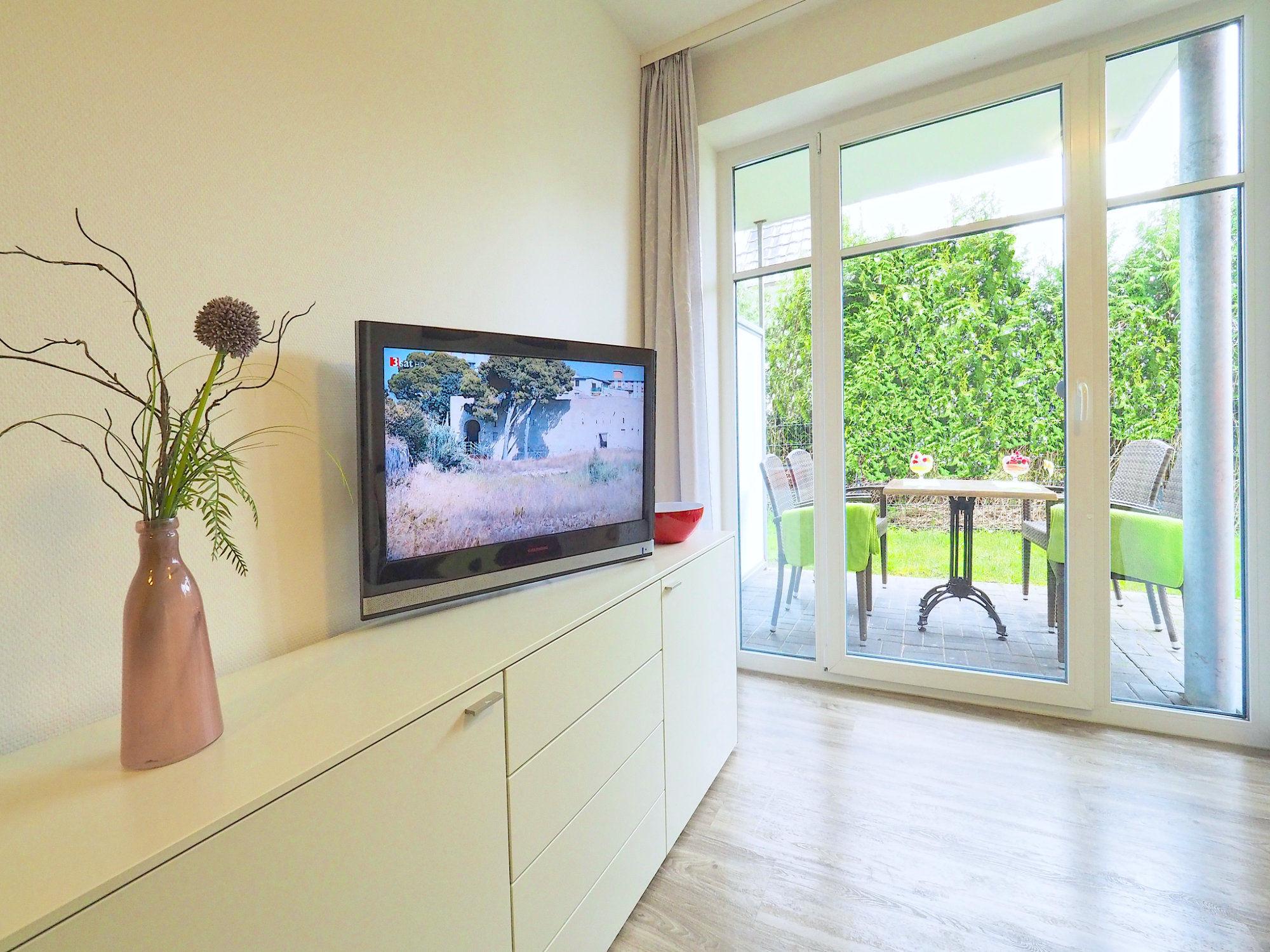 Wohnzimmer mit Sideboard und Flatscreen TV, große Terrassentür