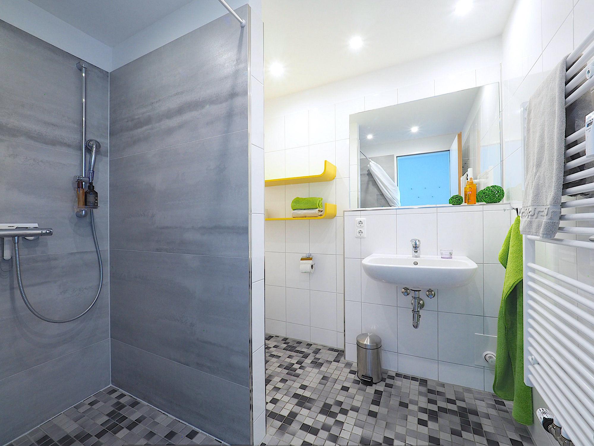 Duschbad mit bodentiefer Dusche, Waschbecken, zwei Regalen und Handtuchheizung
