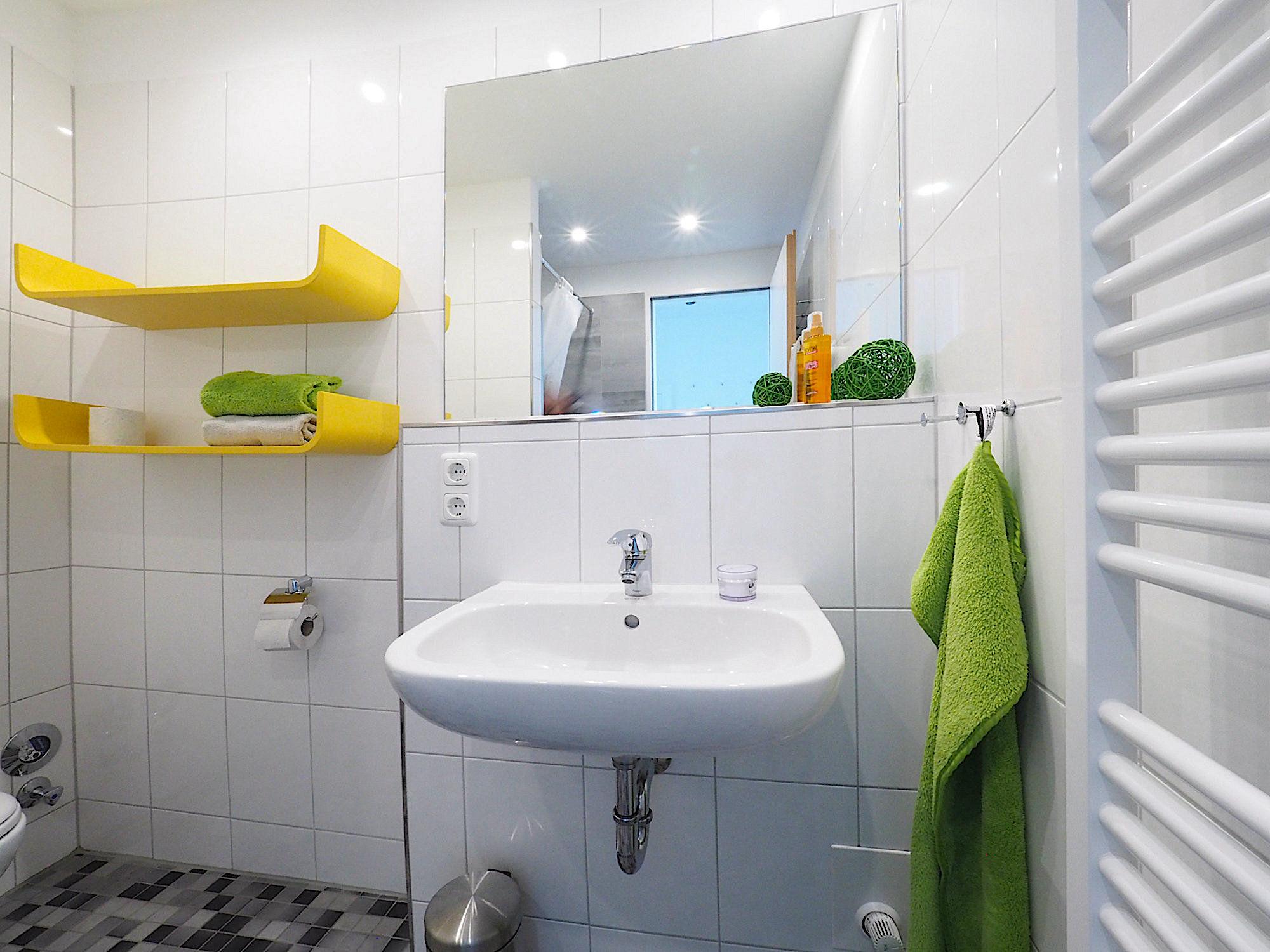 Duschbad mit zwei Regalen, Waschbecken und Handtuchheizung