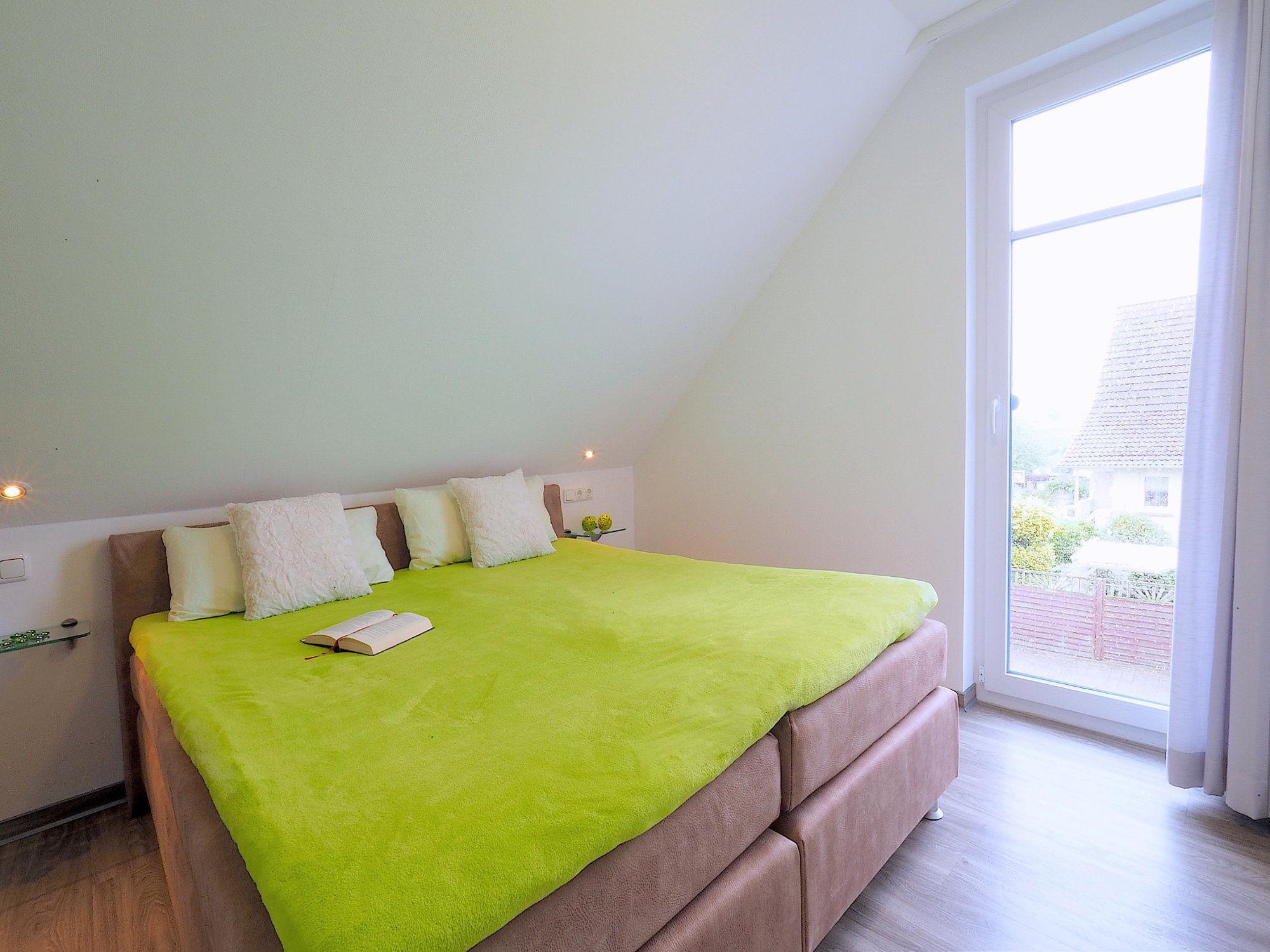 Schlafzimmer mit Doppelbett und bodentiefem Balkonfenster