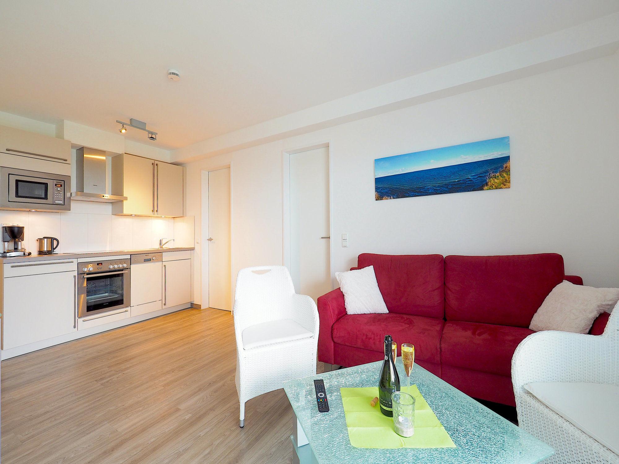 Im Vordergrund Couch mit Glastisch und Korbsessel, moderne Küchenzeile im Hintergrund