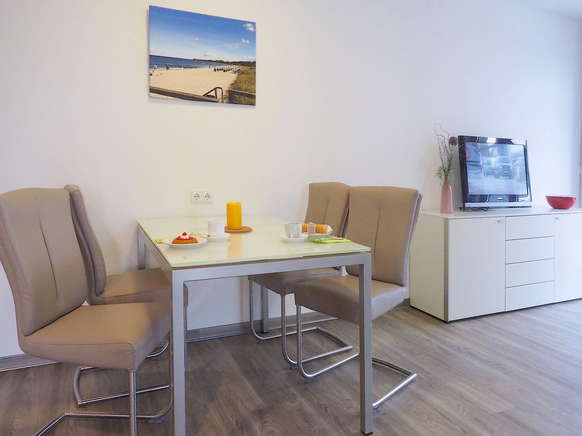 Esstisch mit 4 Stühlen, rechts davon Sideboard mit Flatscreen TV