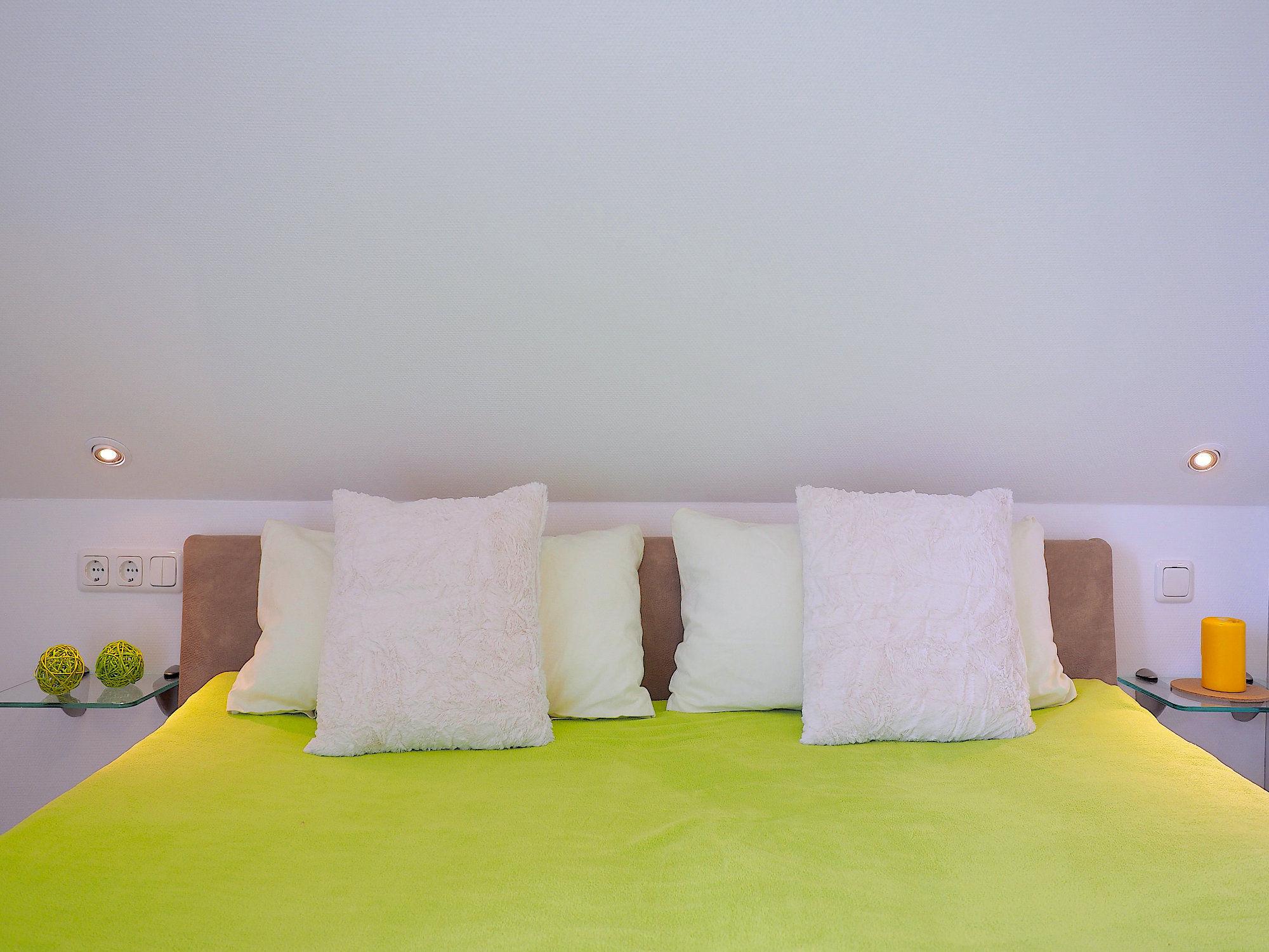 Schlafzimmer mit Doppelbett,   Blick auf das Kopfteil mit Kissen