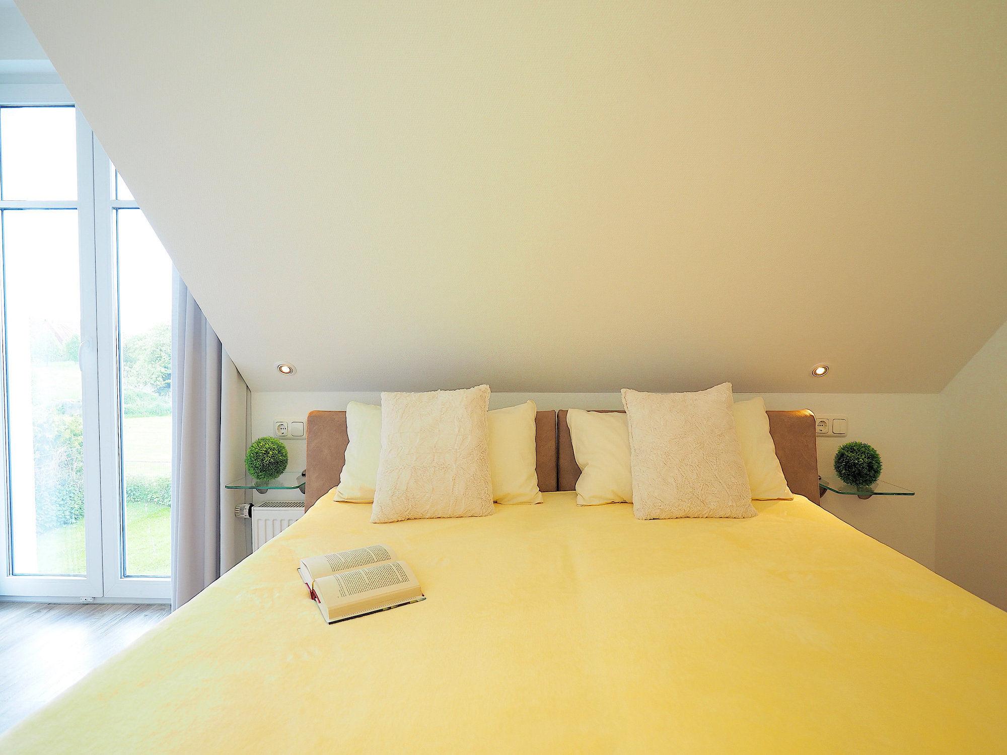 Zweites Schlafzimmer mit Doppelbett und einem bodentiefen Fenster