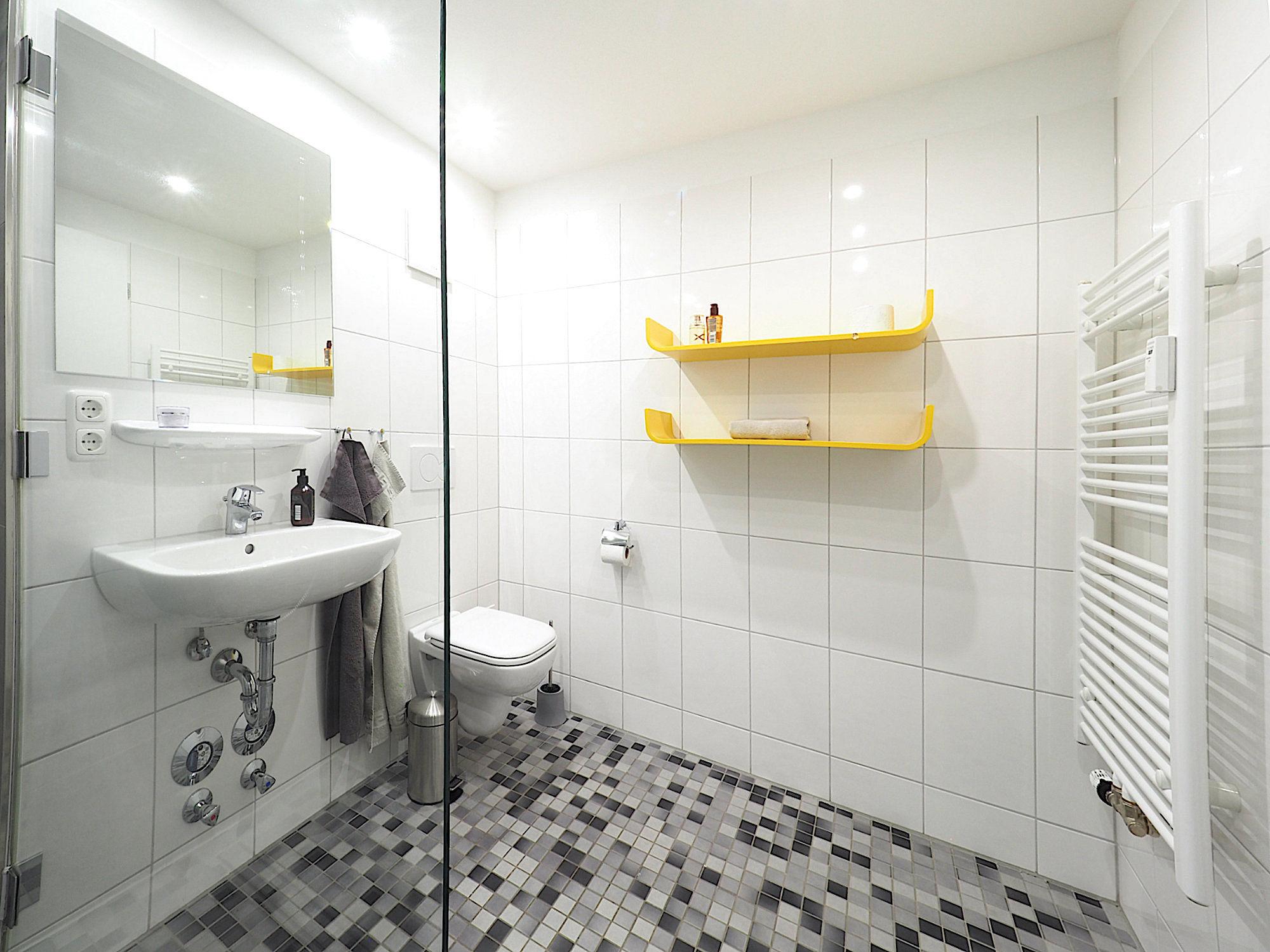 Duschbad mit bodentiefer Dusche, Waschbecken, WC, zwei Regalen und Handtuchheizung