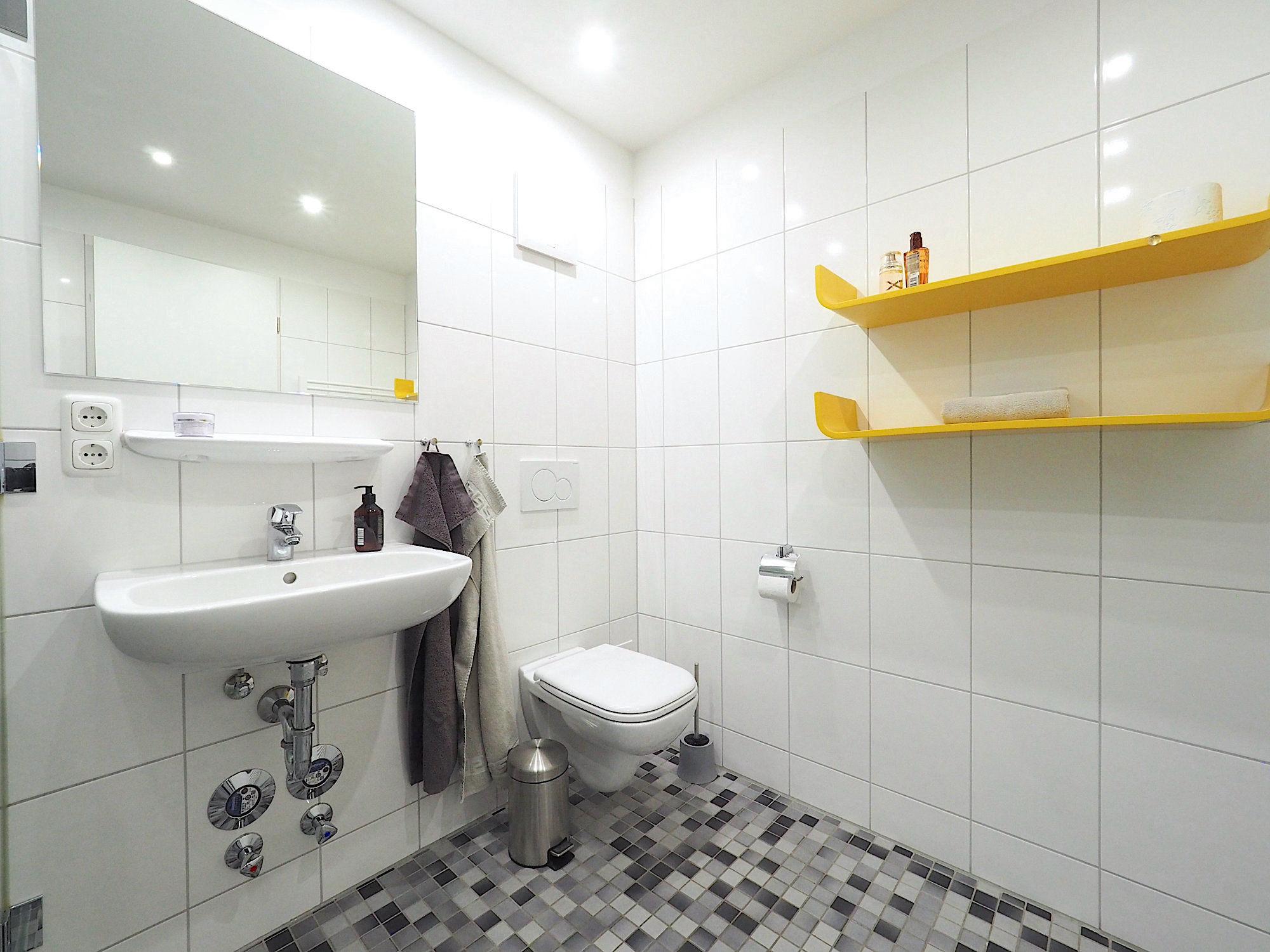 Duschbad mit Dusche, Waschbecken, WC und zwei Regalen