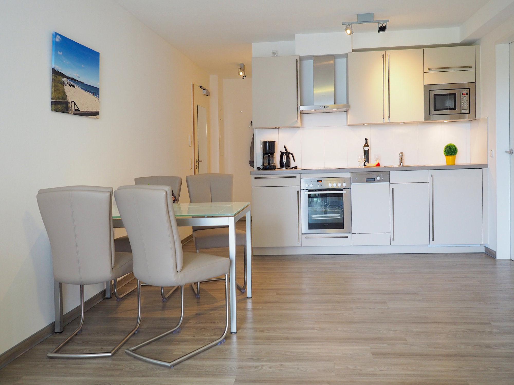 Esstisch mit vier Stühlen, moderne Küchenzeile im Hintergrund