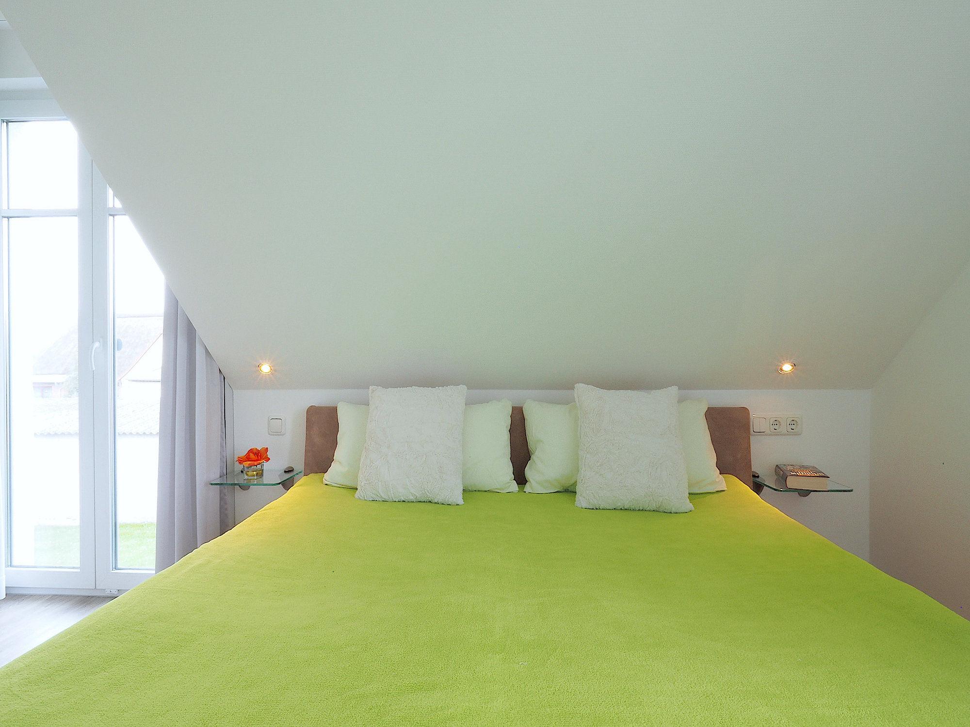 Schlafzimmer mit Doppelbett und bodentiefem Fenster
