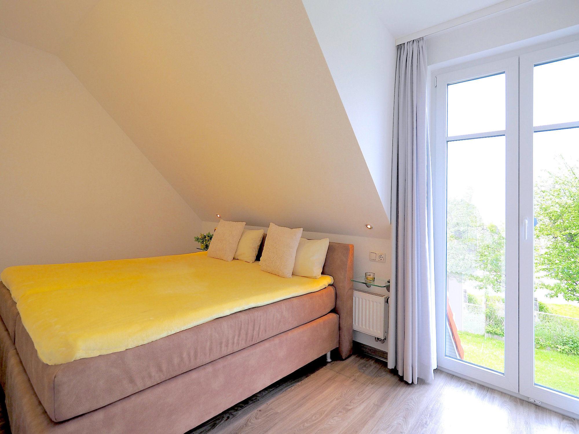 Zweites Schlafzimmer mit Doppelbett und einem großen, bodentiefen Fenster