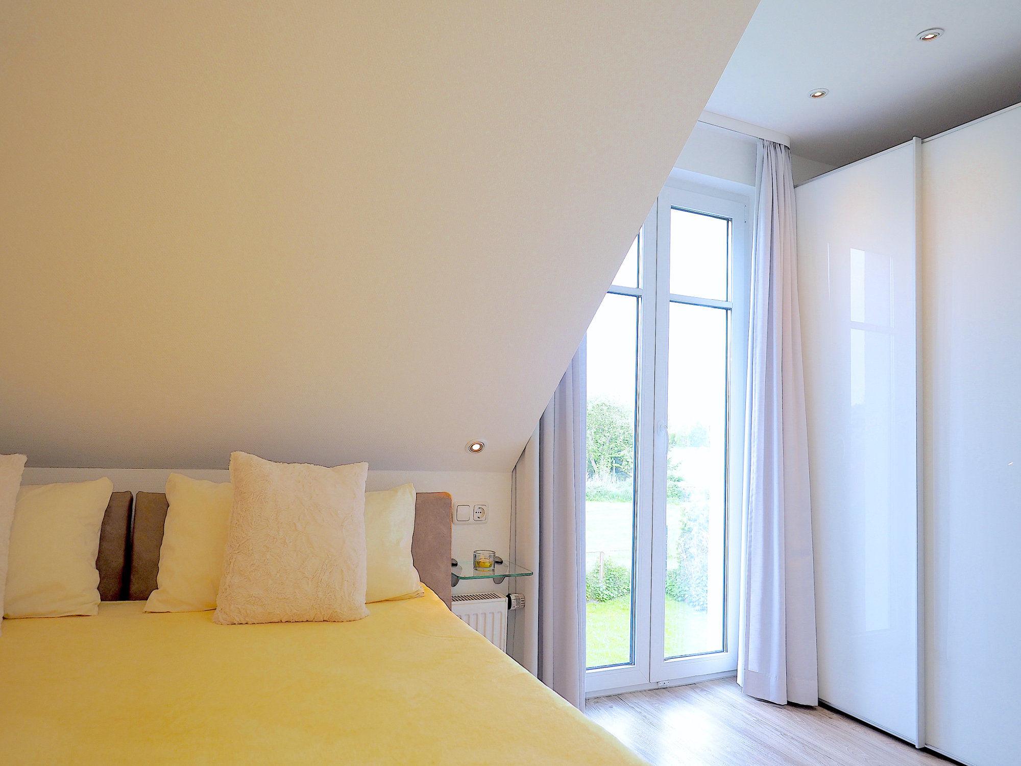 Zweites Schlafzimmer mit Doppelbett und einem bodentiefen Fenster, rechts davon ein Kleiderschrank