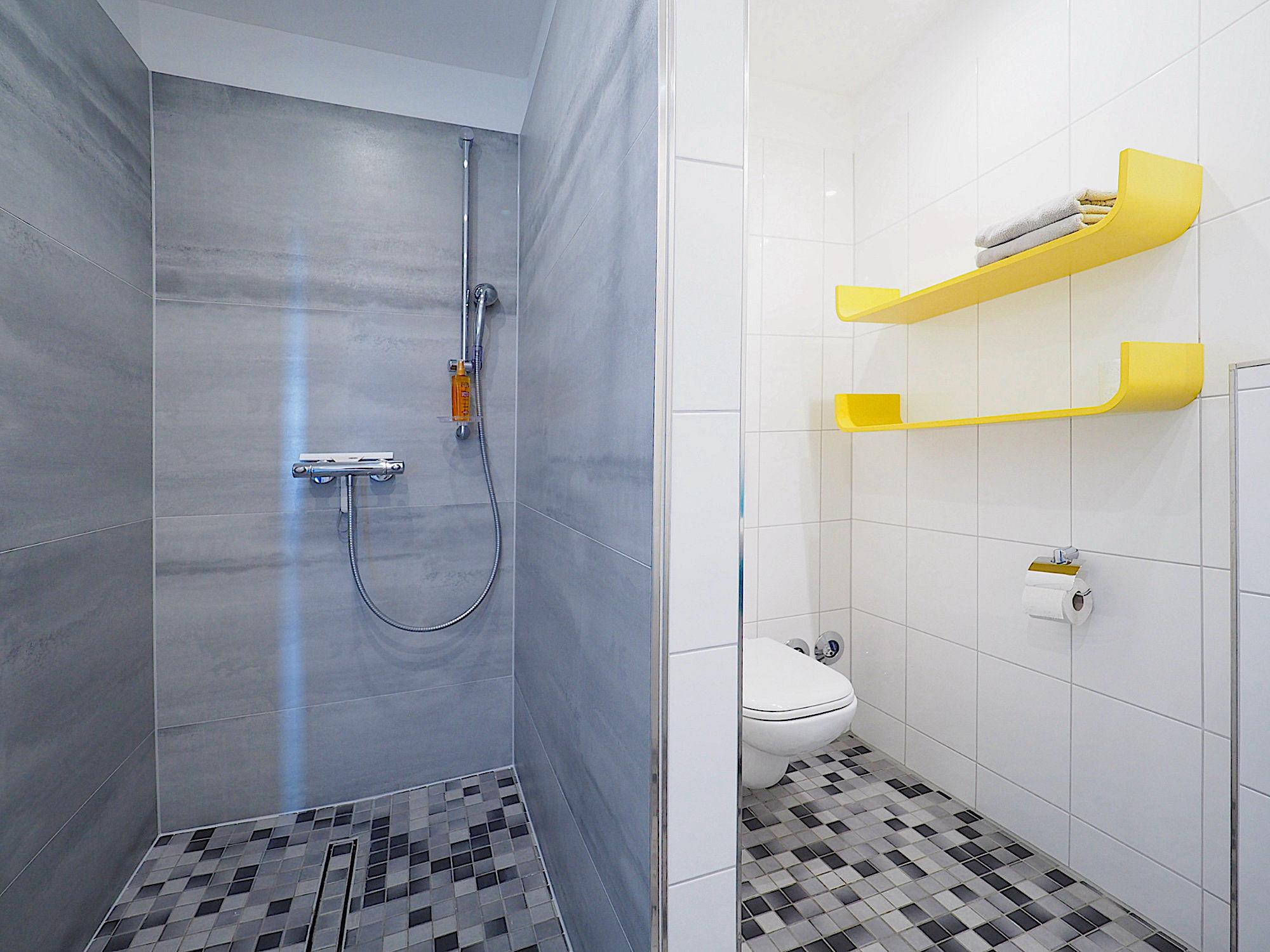 Duschbad mit bodentiefer Dusche, WC und zwei Regalen