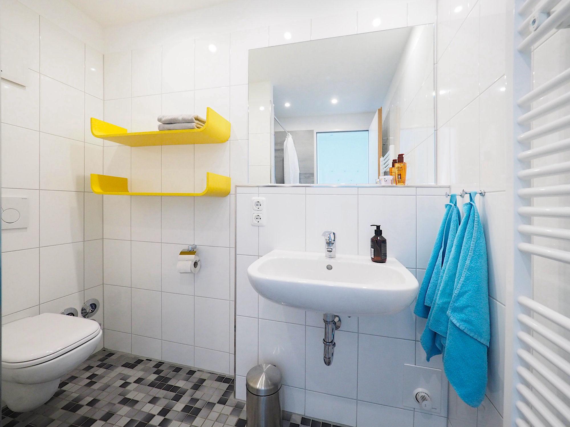 Duschbad mit WC, zwei Regalen, Waschbecken und Handtuchheizung