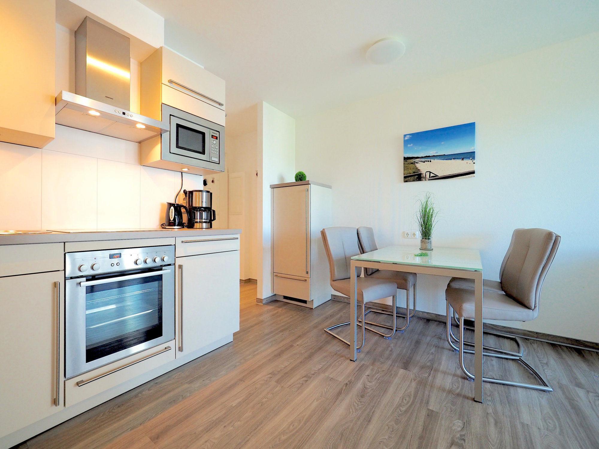 Esstisch mit vier Stühlen, links davon moderne Küchenzeile