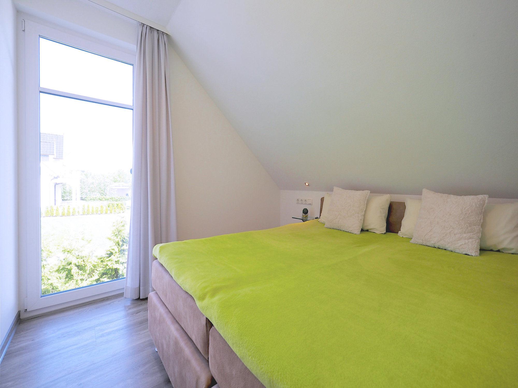 Zweites Schlafzimmer mit Doppelbett und bodentiefem Fenster