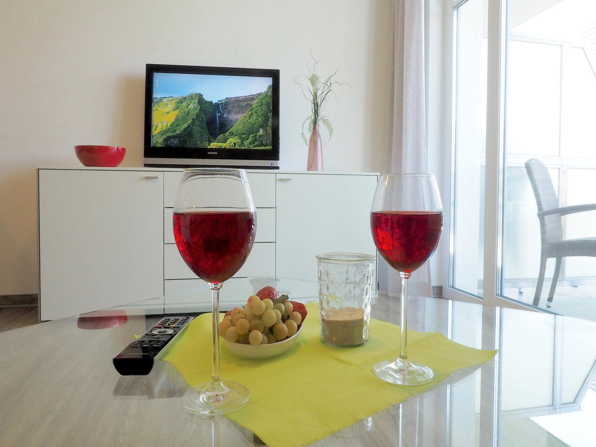 Wohnzimmer Glastisch mit Blick zum Flatscreen TV und Sideboard