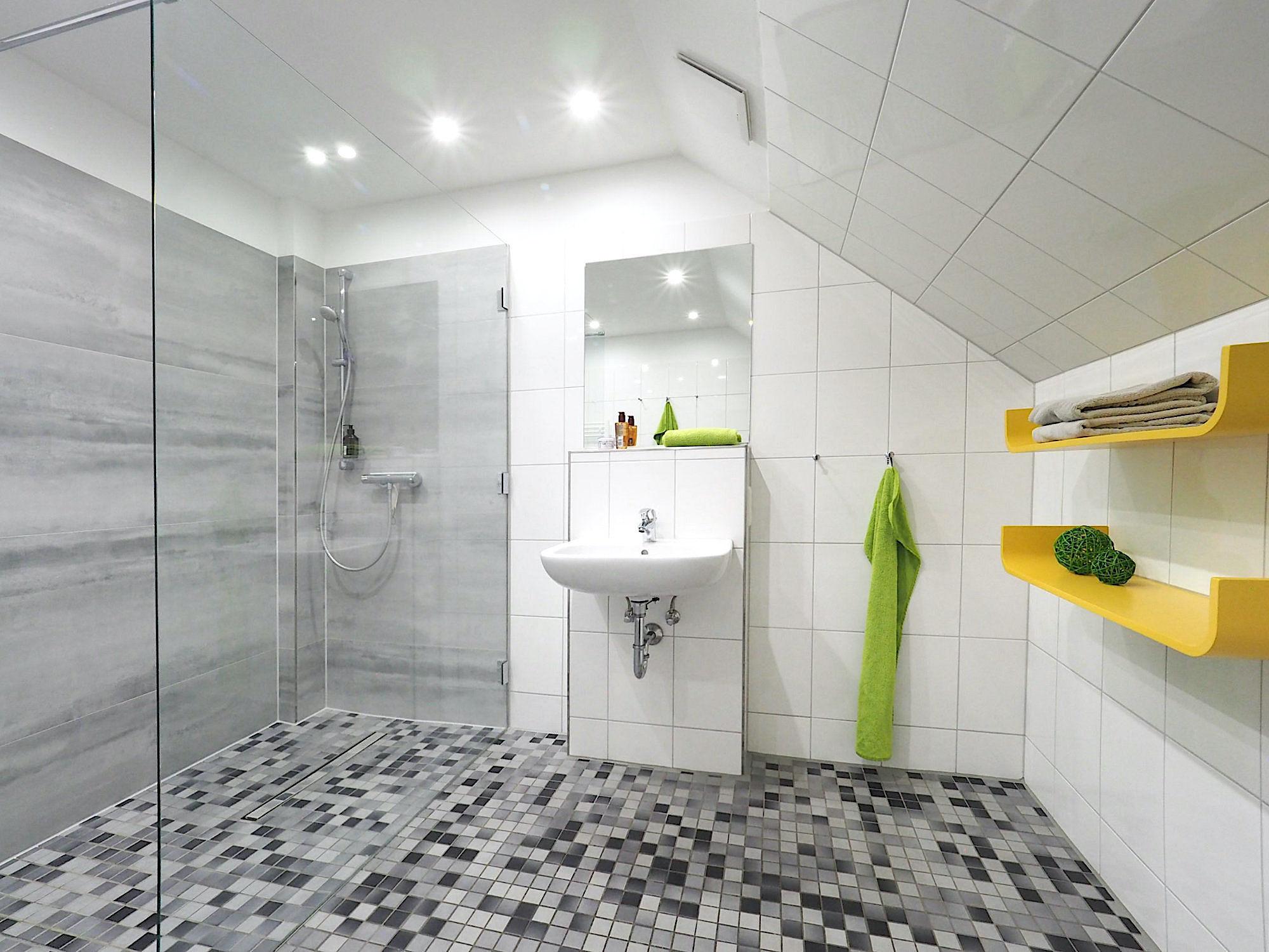 Duschbad mit bodentiefer Dusche, Waschbecken und zwei Regalen