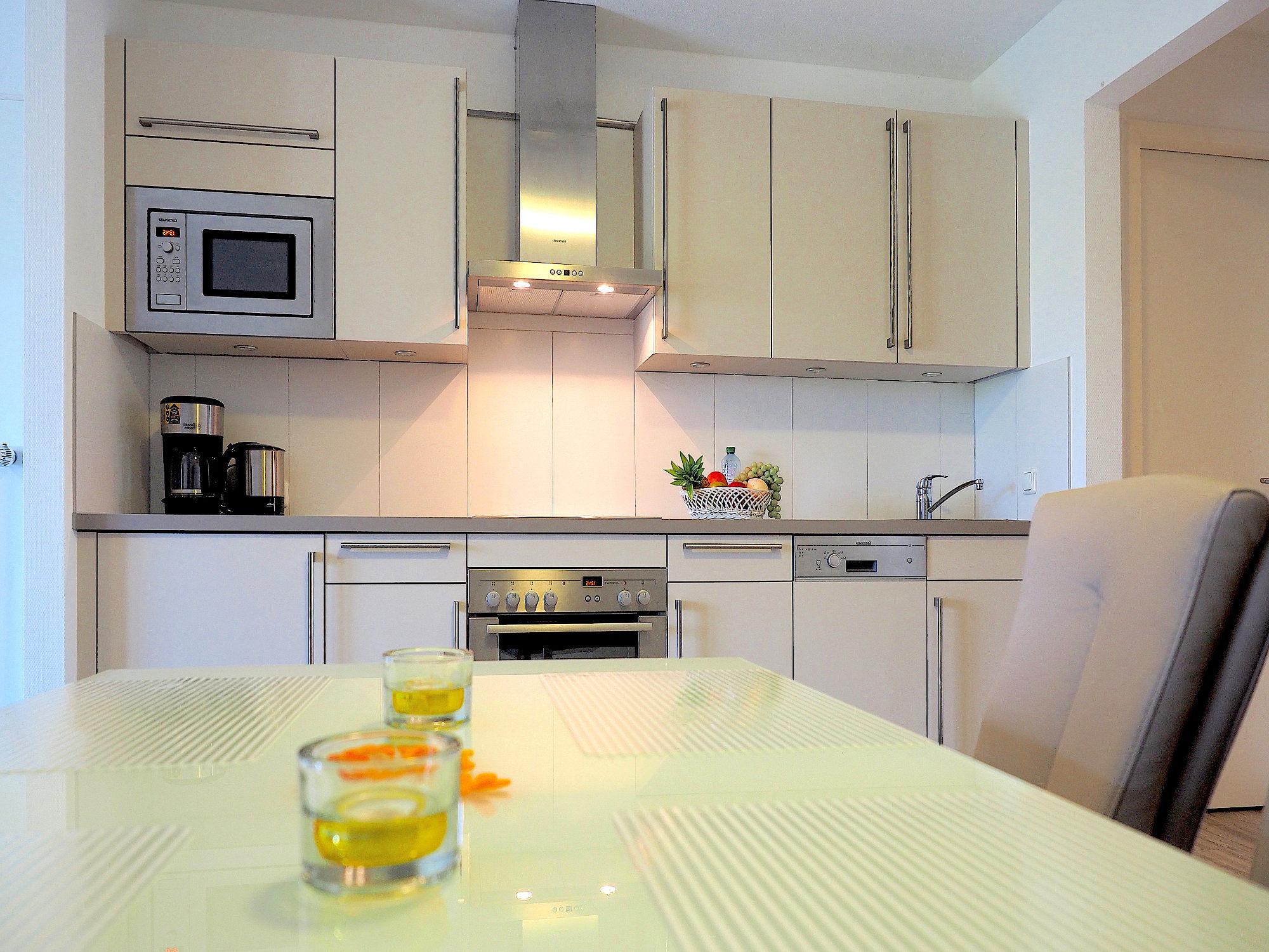 Esstisch, dahinter moderne Küchenzeile