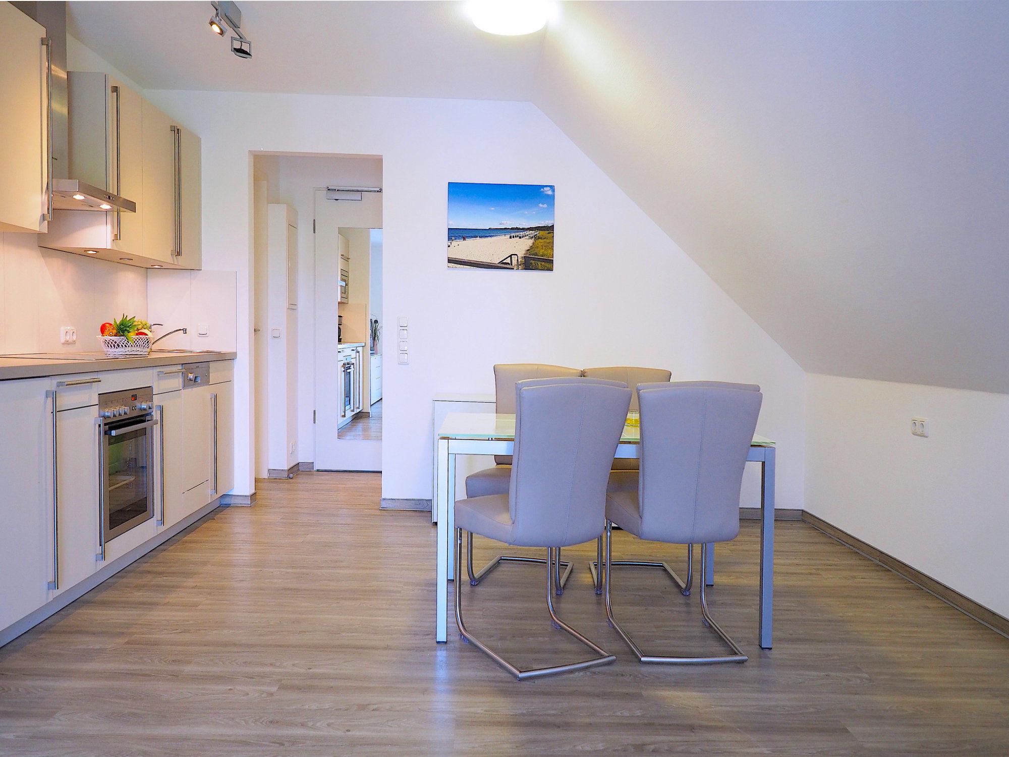Esstisch mit 4 Stühlen und links davon moderne Küchenzeile