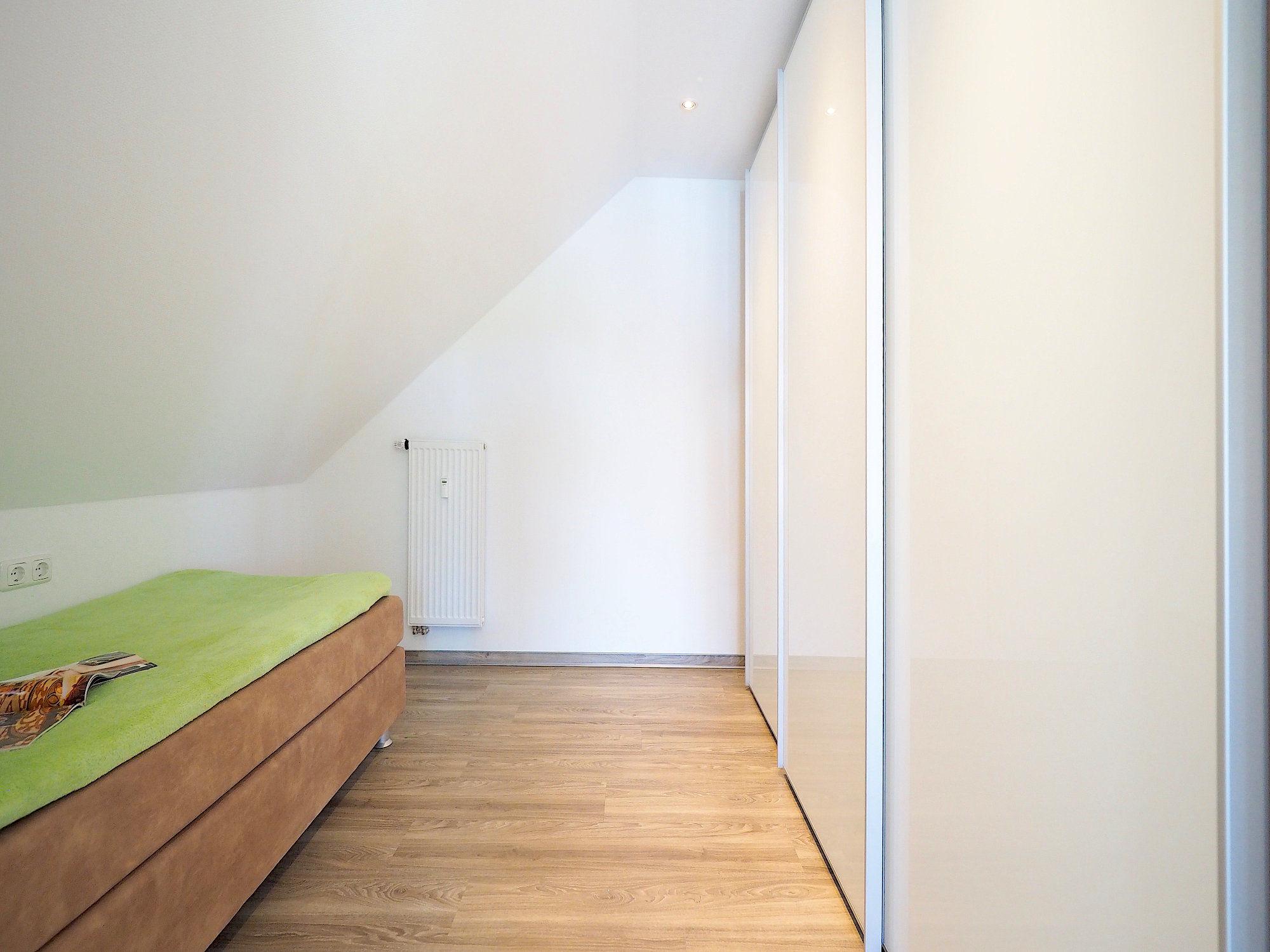 Schlafzimmer mit einem Einzelbett, rechts daneben großer Kleiderschrank