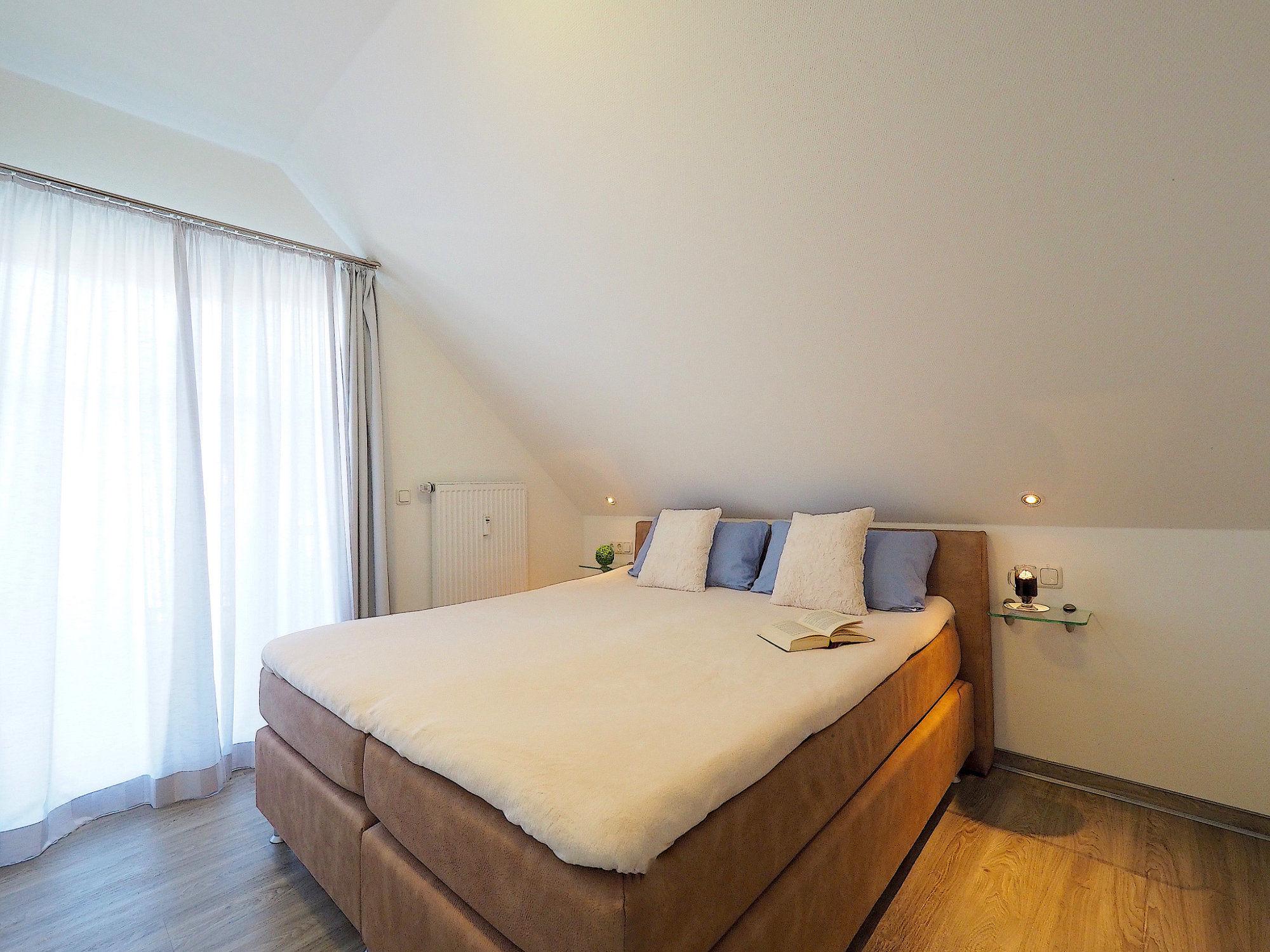 Schlafzimmer mit Doppelbett, links davon bodentiefes Fenster