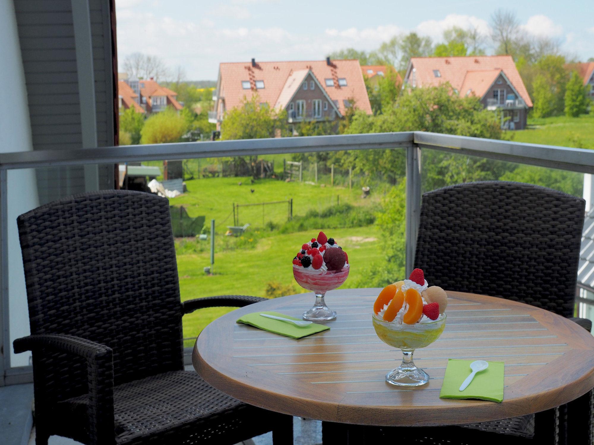 Balkon mit Tisch und zwei Stühlen, Blick ins Grüne