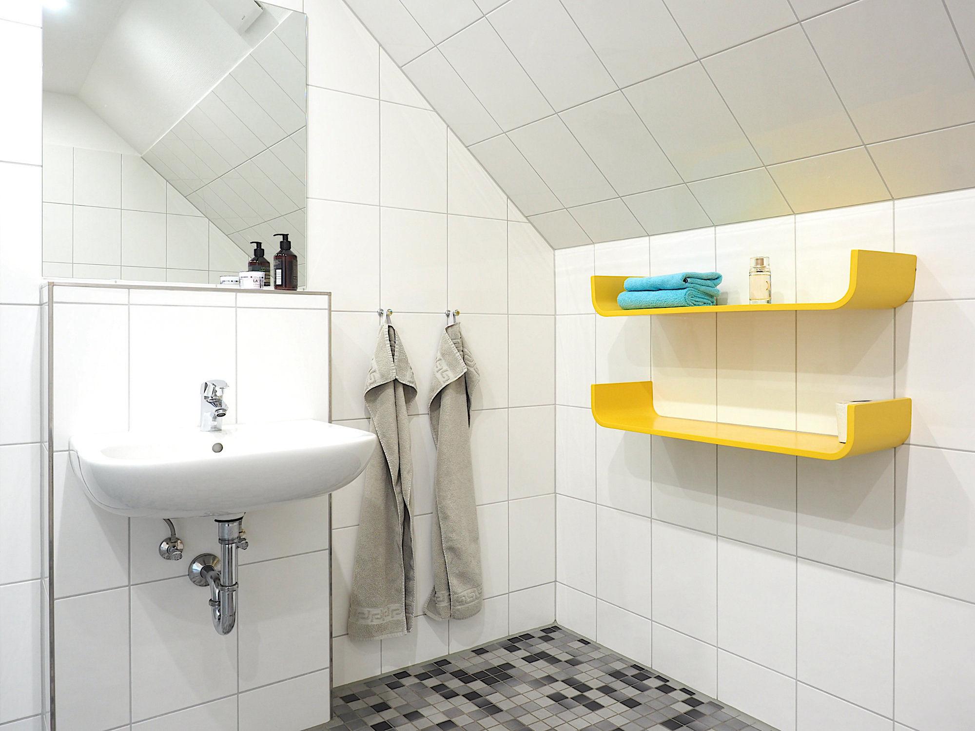 Duschbad mit Waschbecken und zwei Regalen