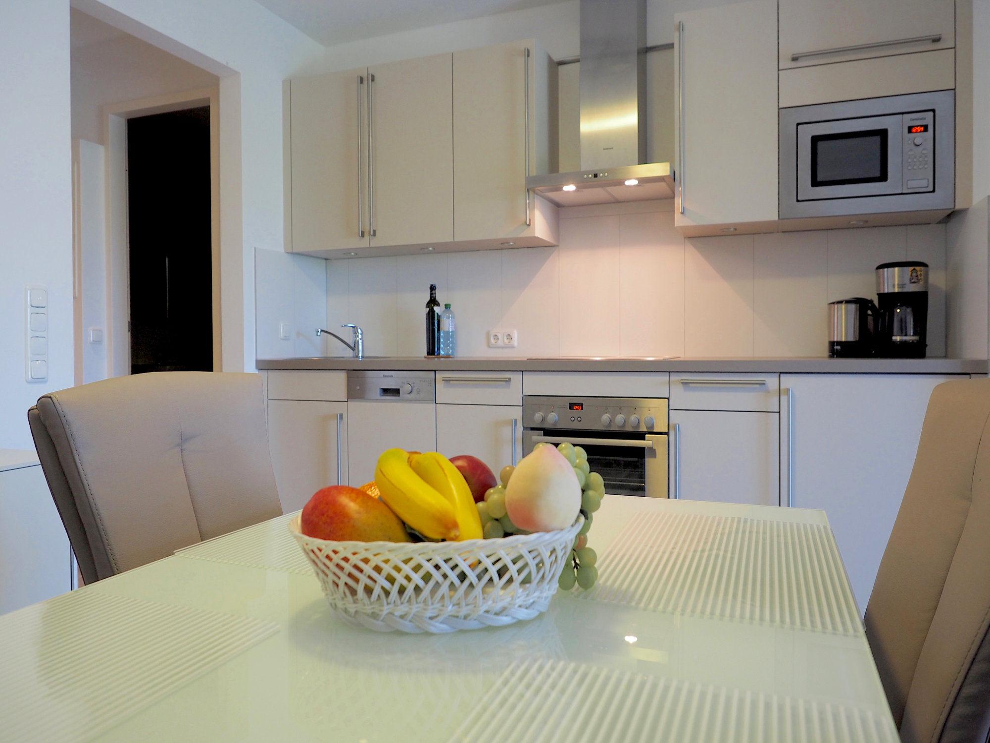 Esstisch mit 4 Stühlen und moderner Küchenzeile im Hintergrund