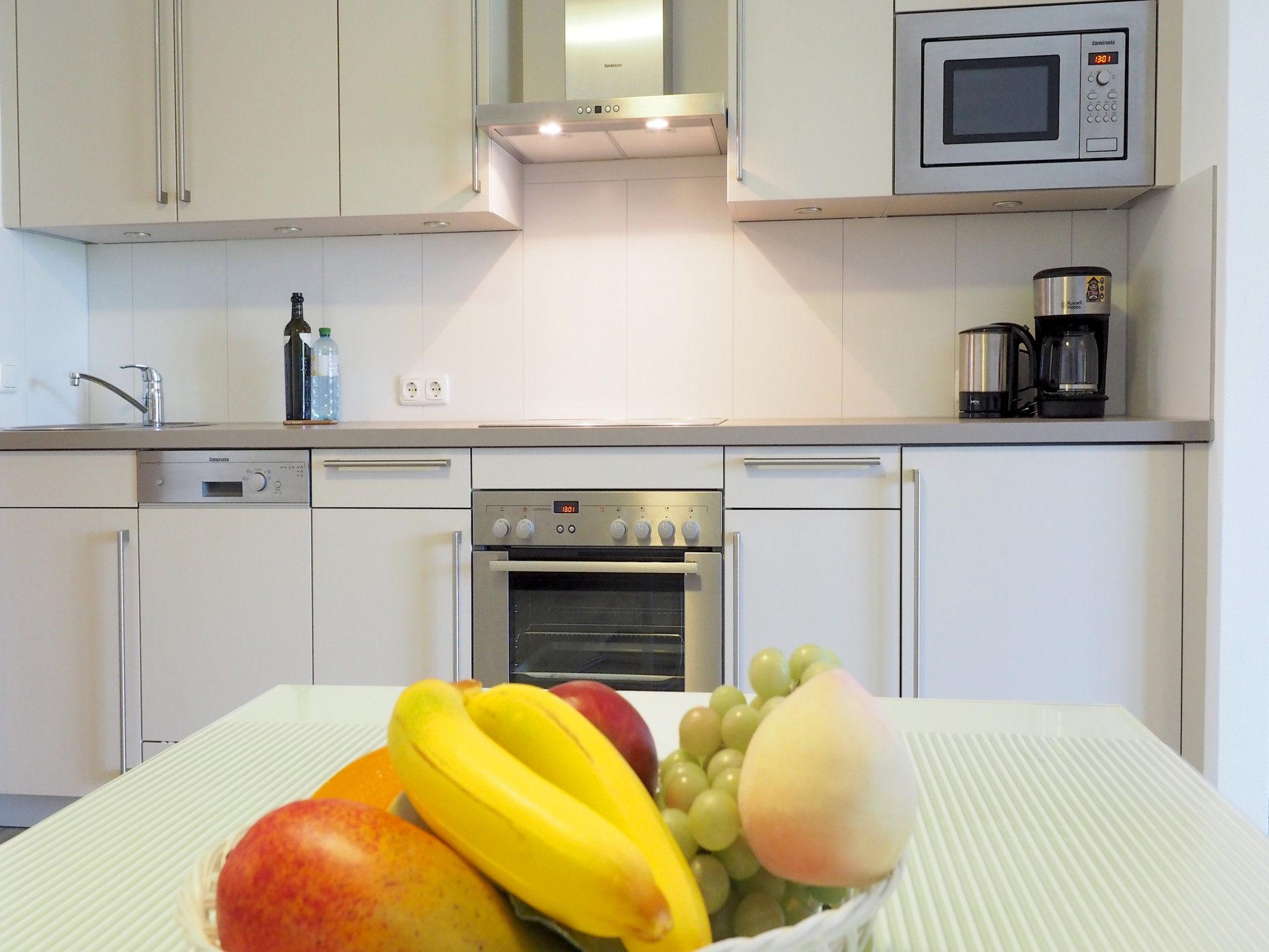 Esstisch mit Obstkorb und moderner Küchenzeile im Hintergrund
