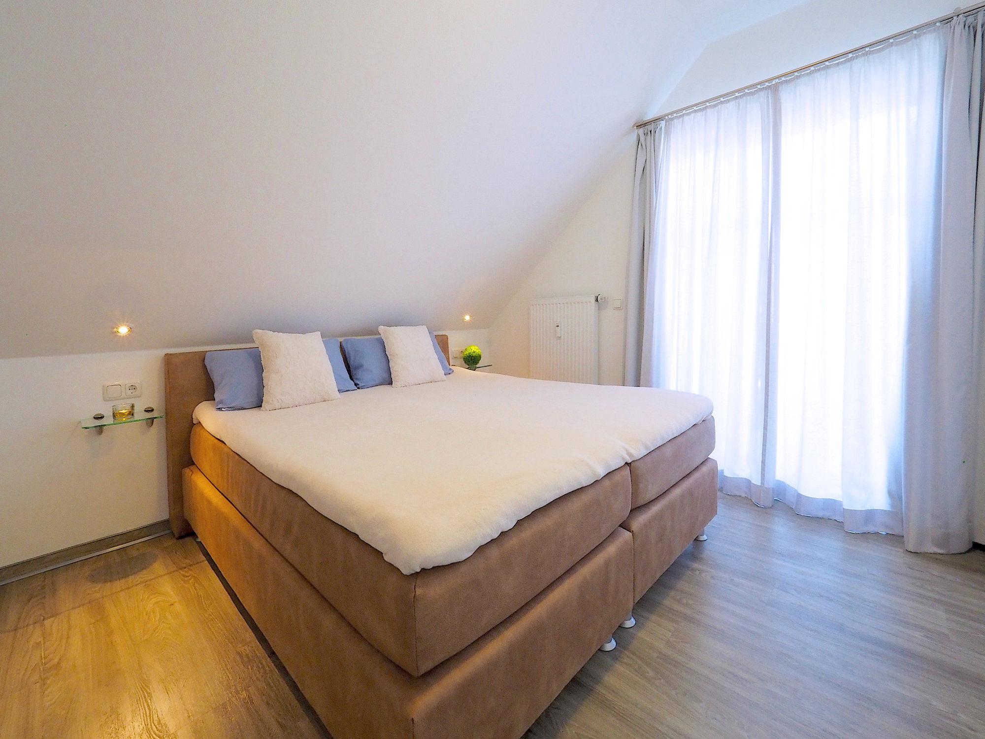 Schlafzimmer mit Doppelbett, rechts davon bodentiefes Fenster