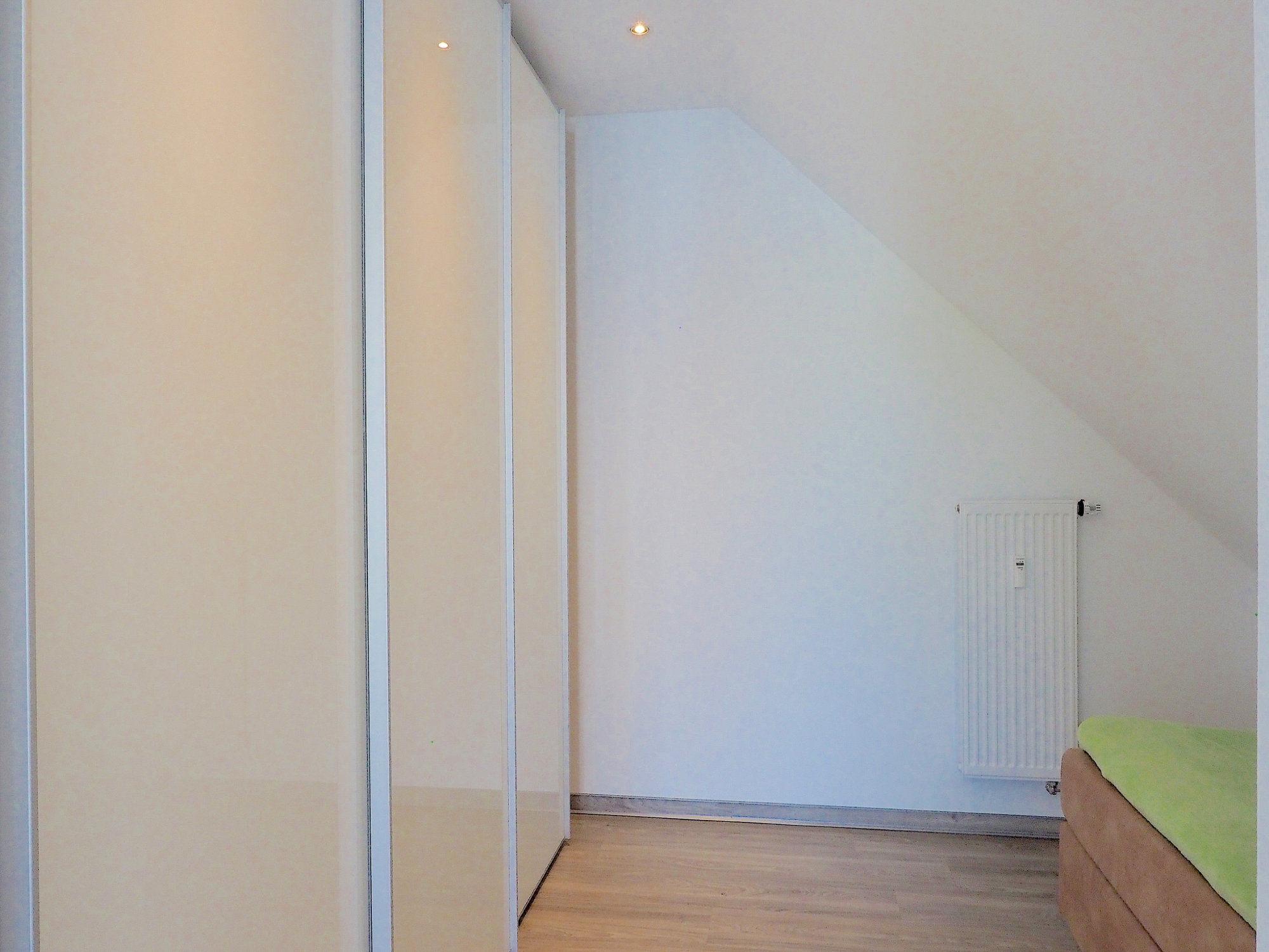 Schlafzimmer mit einem Einzelbett, links davon ein großer Kleiderschrank