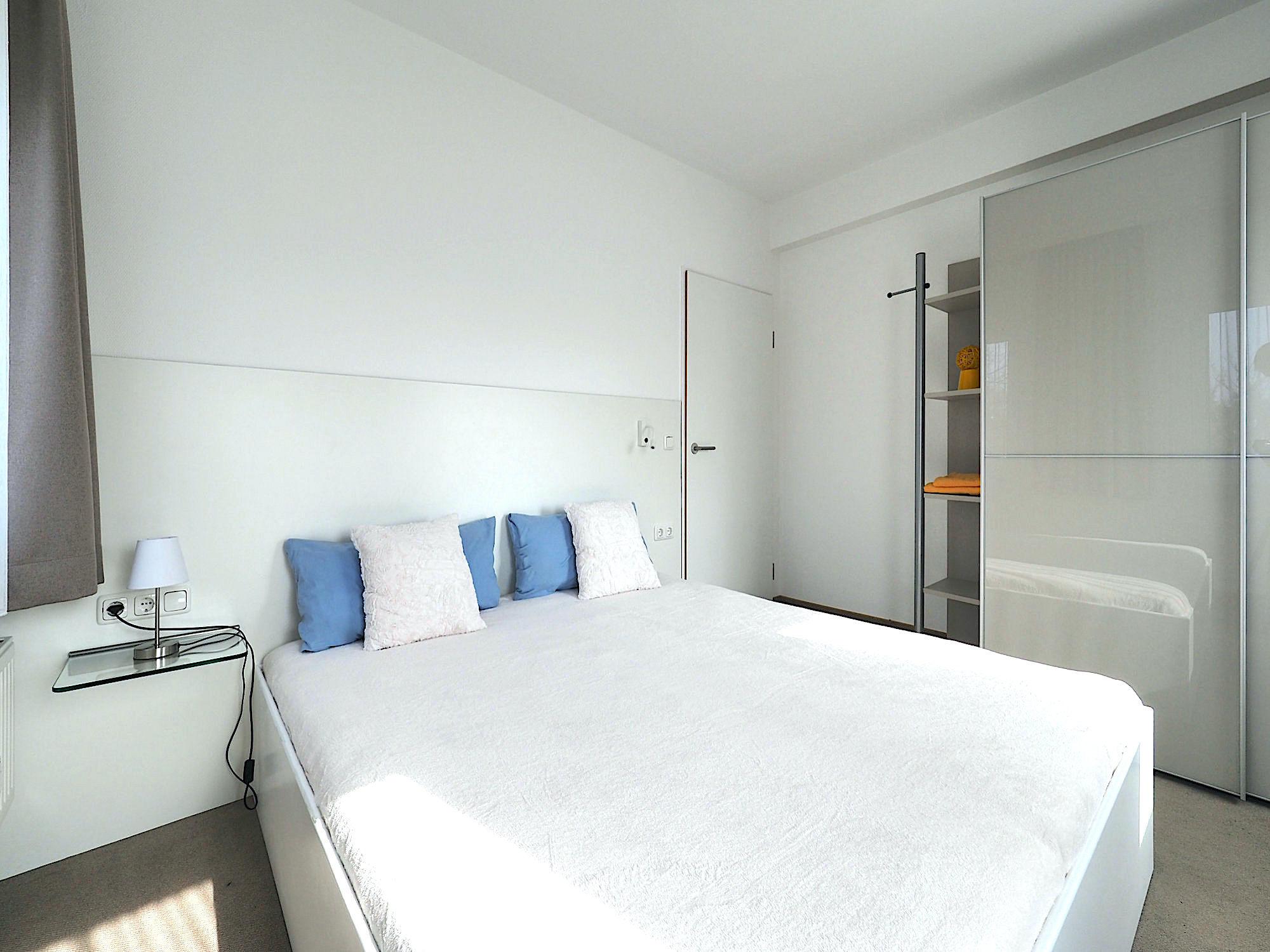 Zweites Schlafzimmer mit Doppelbett, rechts davon ein großer Kleiderschrank mit Regalteil