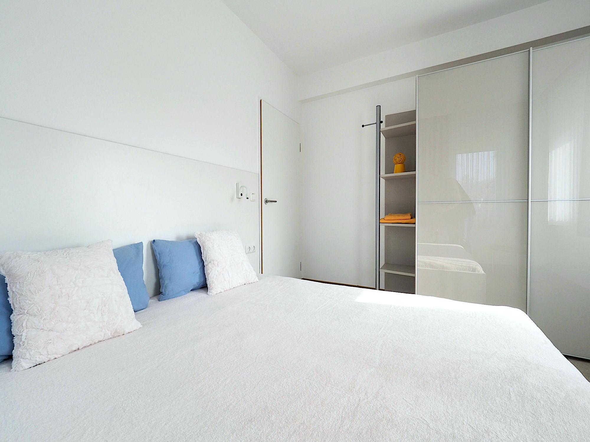 Zweites Schlafzimmer mit Doppelbett, rechts davon ein großer Kleiderschrank mit Schiebetüren und Regalteil