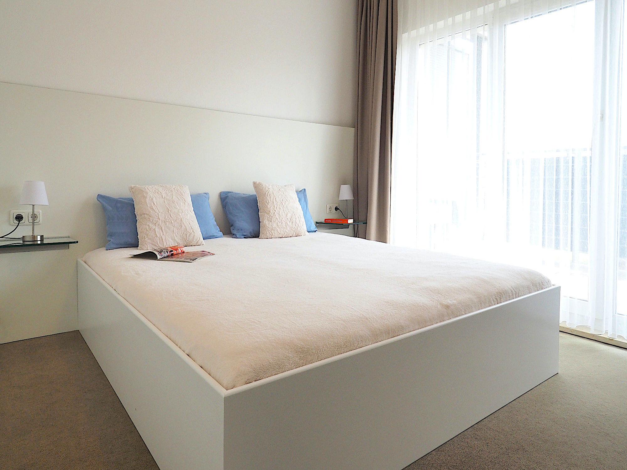 Schlafzimmer mit Doppelbett, rechts davon bodentiefe Fenster