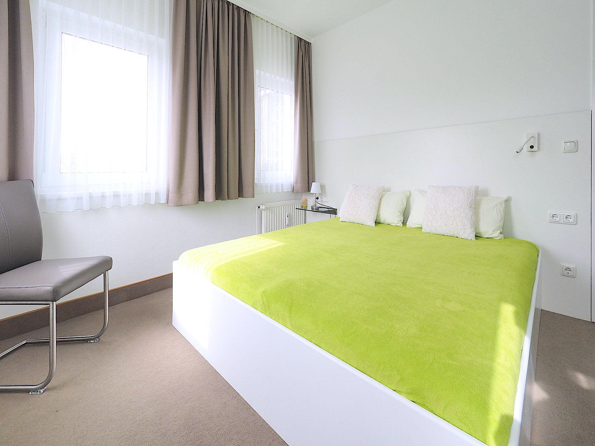 Zweites Schlafzimmer mit Doppelbett, im Hintergrund zwei Fenster