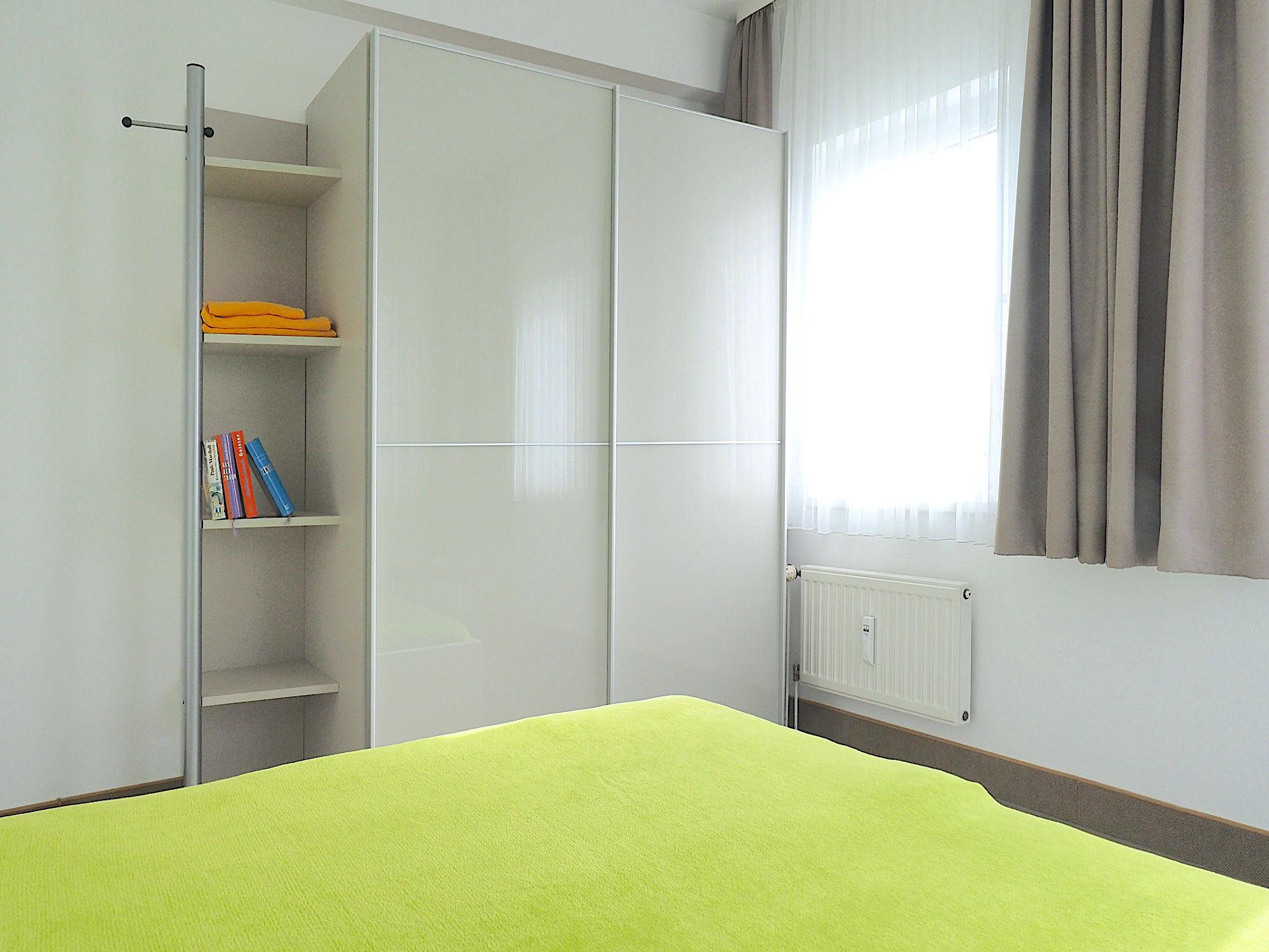 Zweites Schlafzimmer mit Doppelbett, dahinter ein großer Kleiderschrank mit Regalteil, rechts ein Fenster