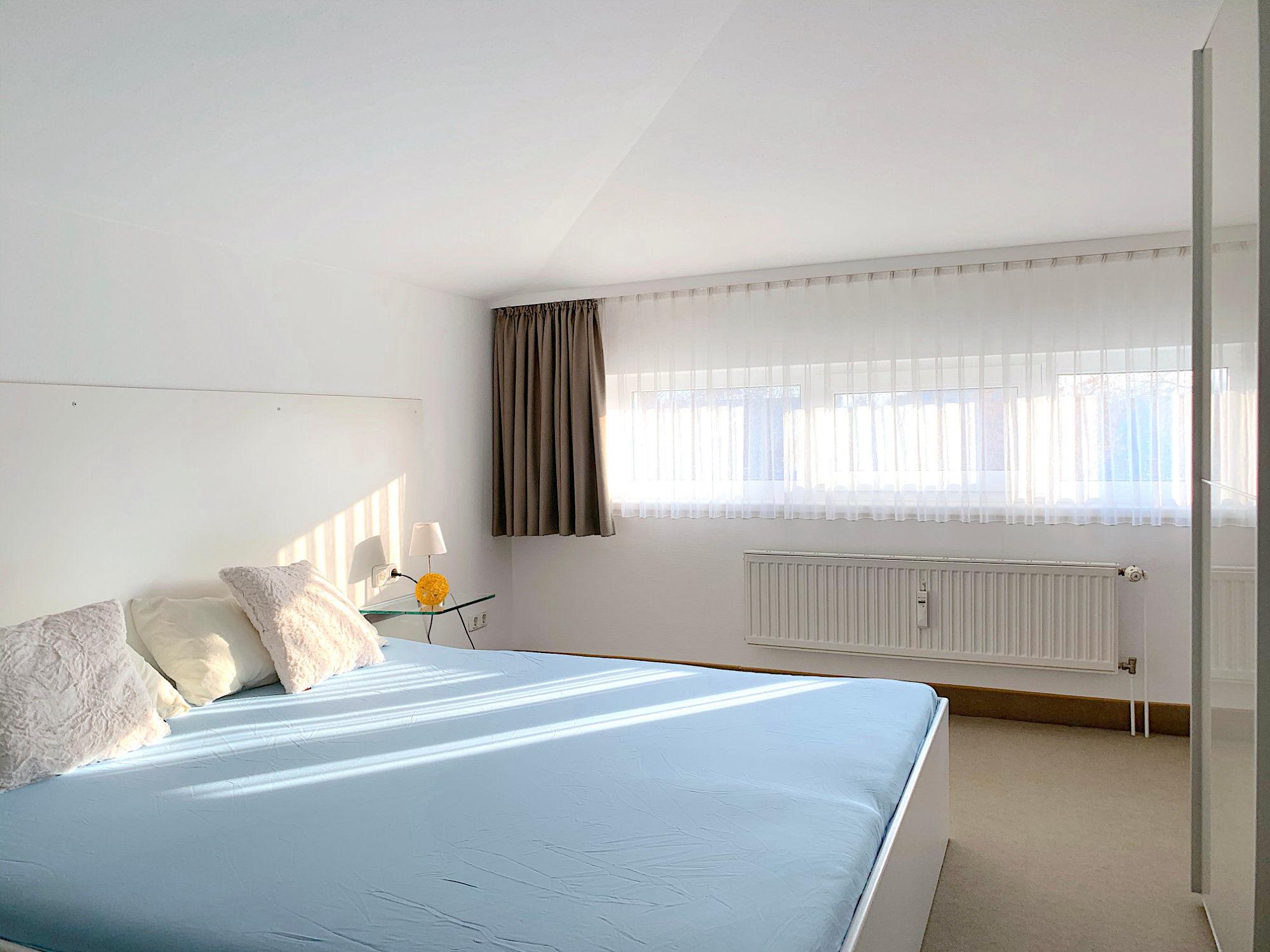 Schlafzimmer mit Doppelbett, rechts davon ein großer Kleiderschrank, im Hintergrund sind Fenster