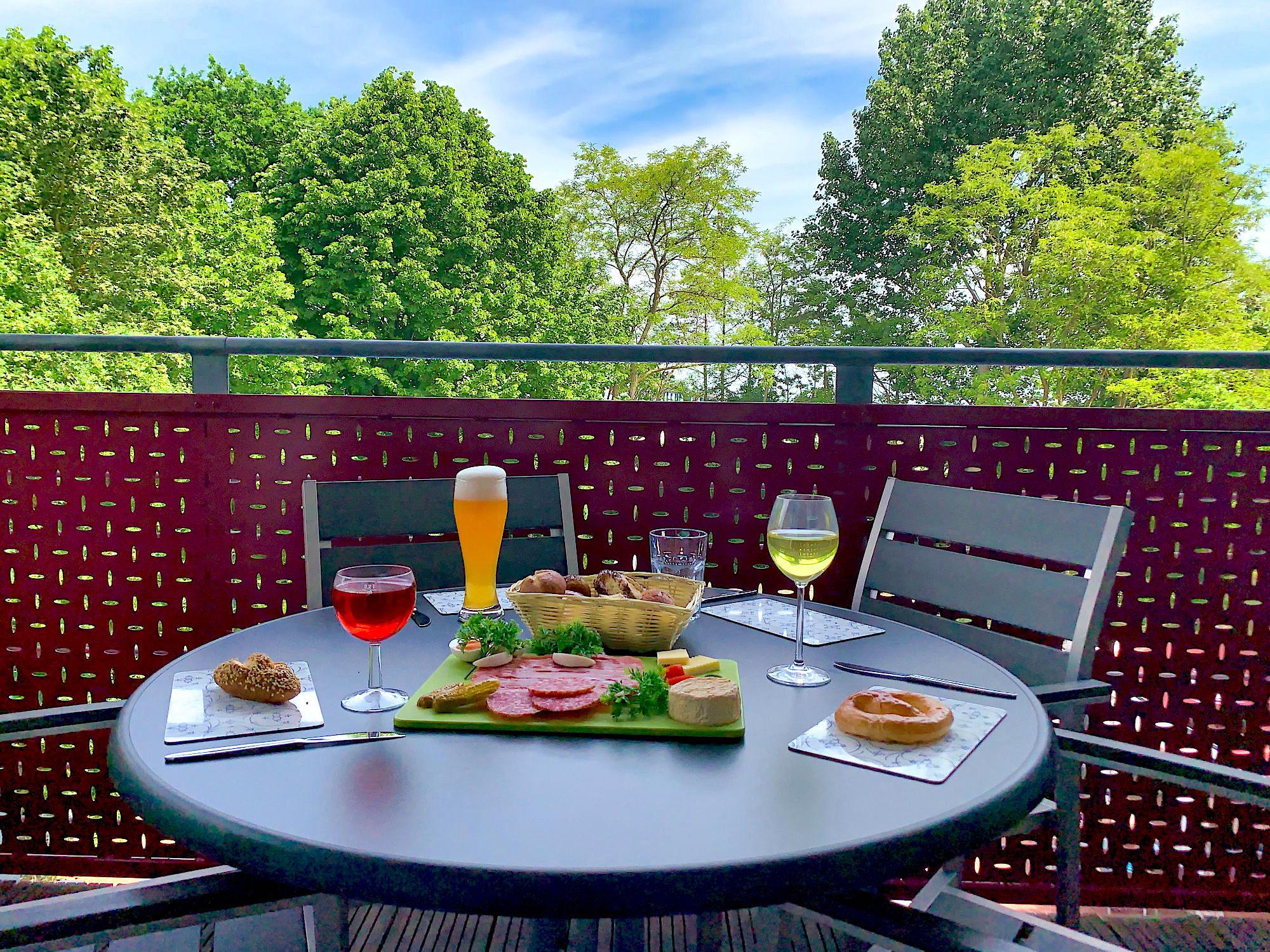 Balkon mit Tisch und Stühlen und Blick ins Grüne zum Küstenschutzstreifen