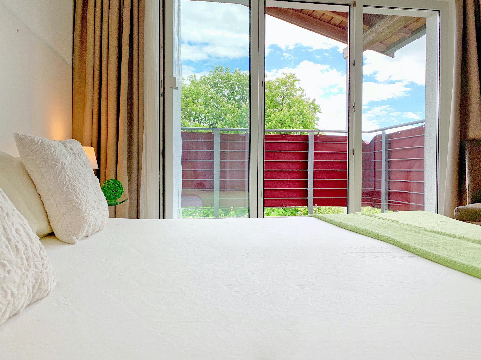 Schlafzimmer mit Doppelbett, im Hintergrund bodentiefe Fenster und Zugang zum Balkon