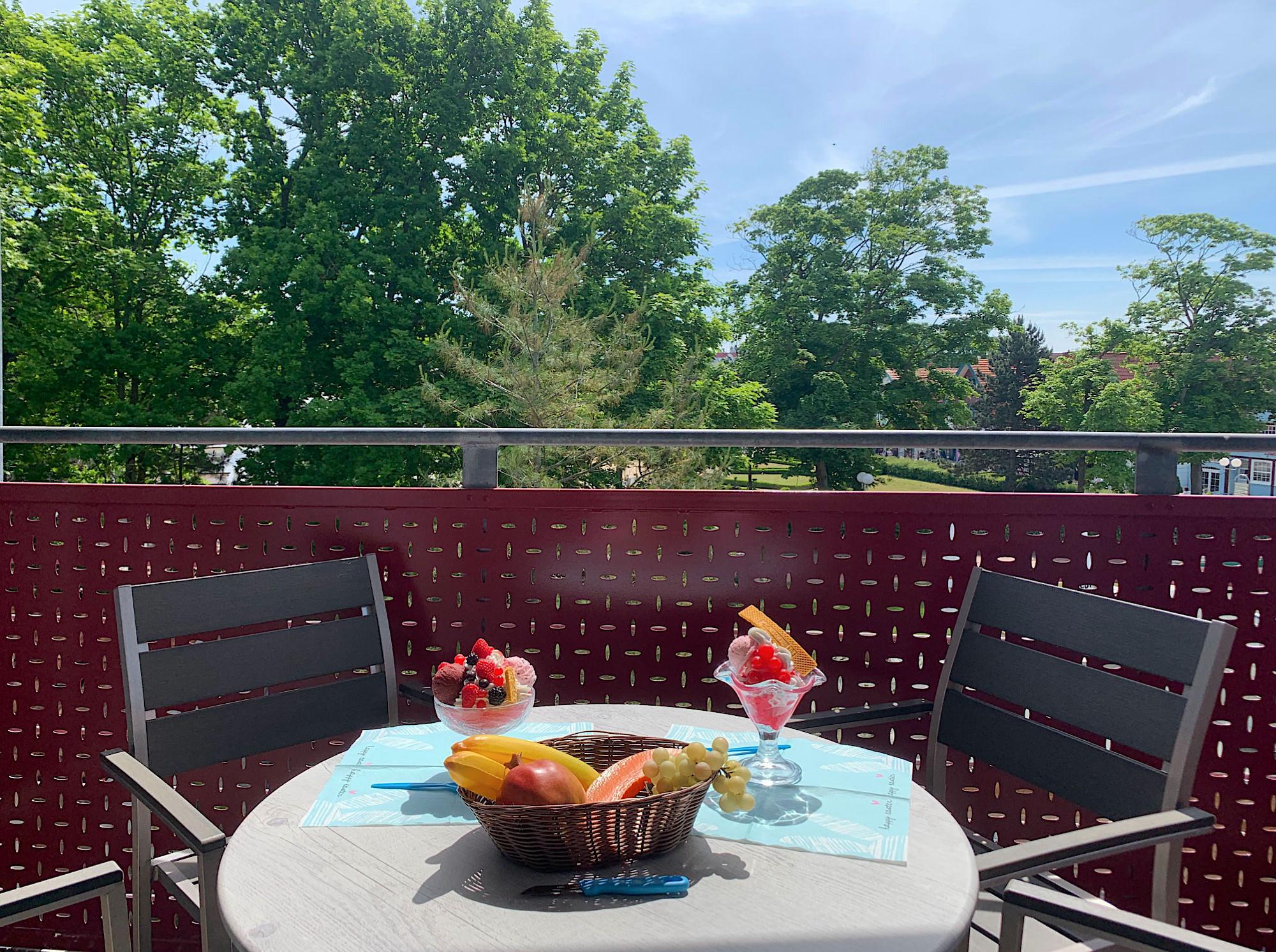 Balkon mit Tisch und Stühlen, Blick ins Grüne, im Hintergrund ist der Kurpark zu sehen