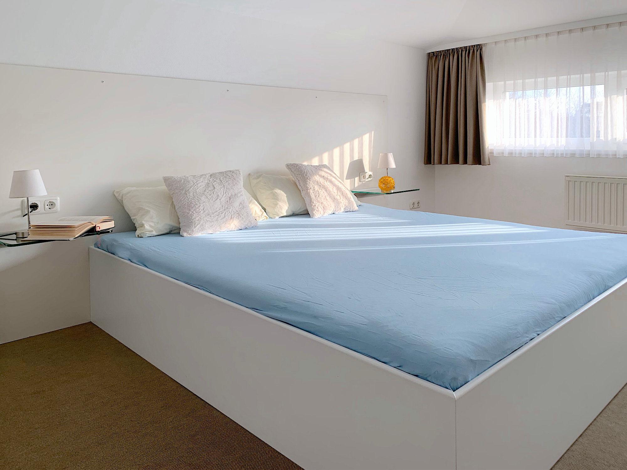Schlafzimmer mit Doppelbett, rechts davon ein langgestrecktes Fenster