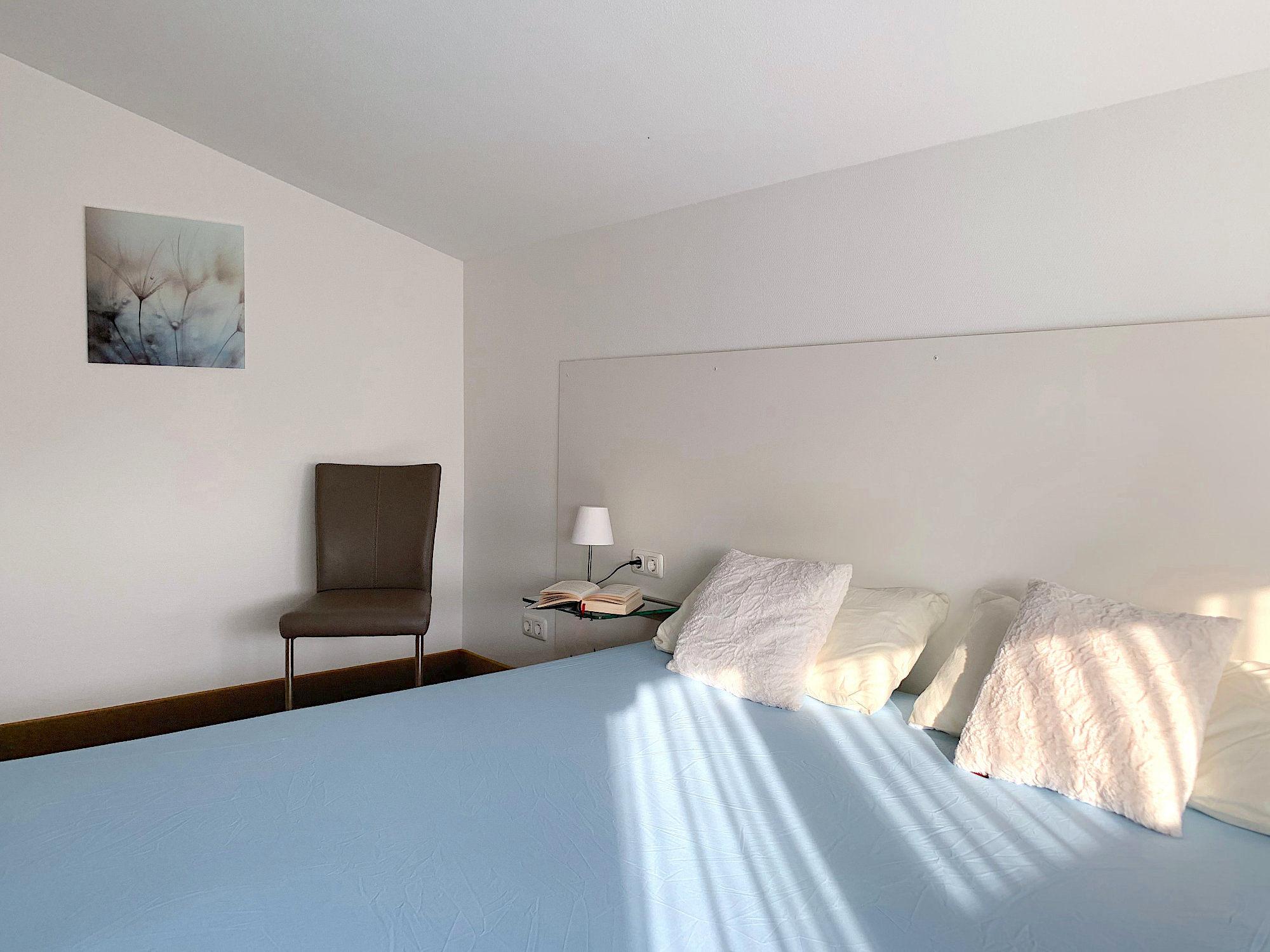 Schlafzimmer mit Doppelbett, links davon steht ein Stuhl
