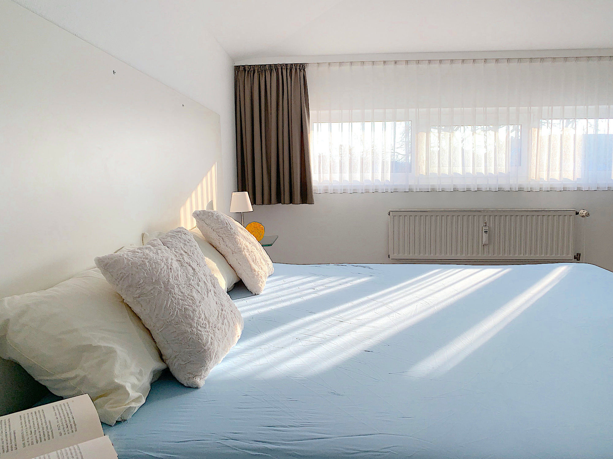 Schlafzimmer mit Doppelbett, rechts davon ein großes Fenster